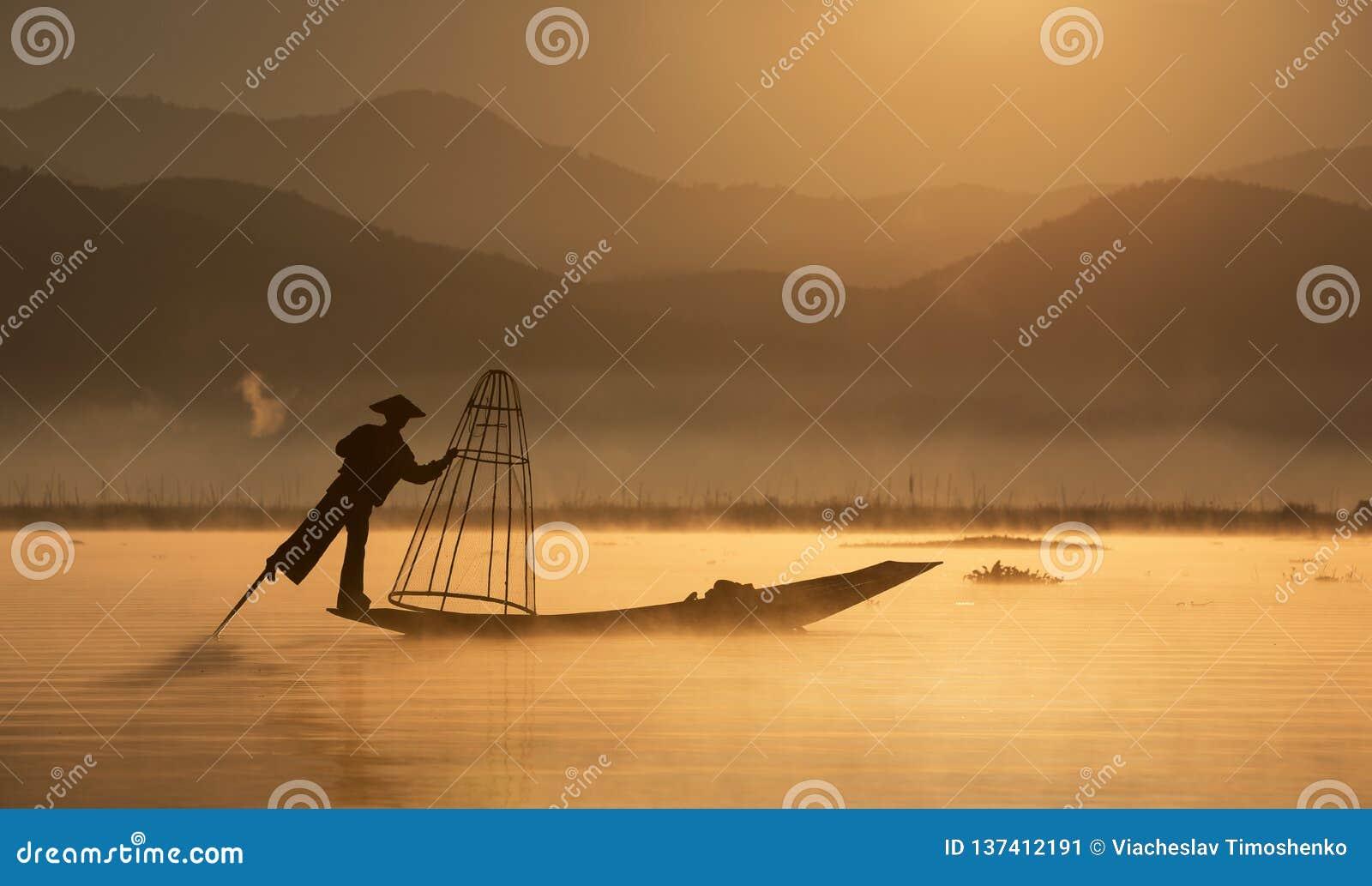 Pescador com rede tradicional no barco velho no alvorecer a