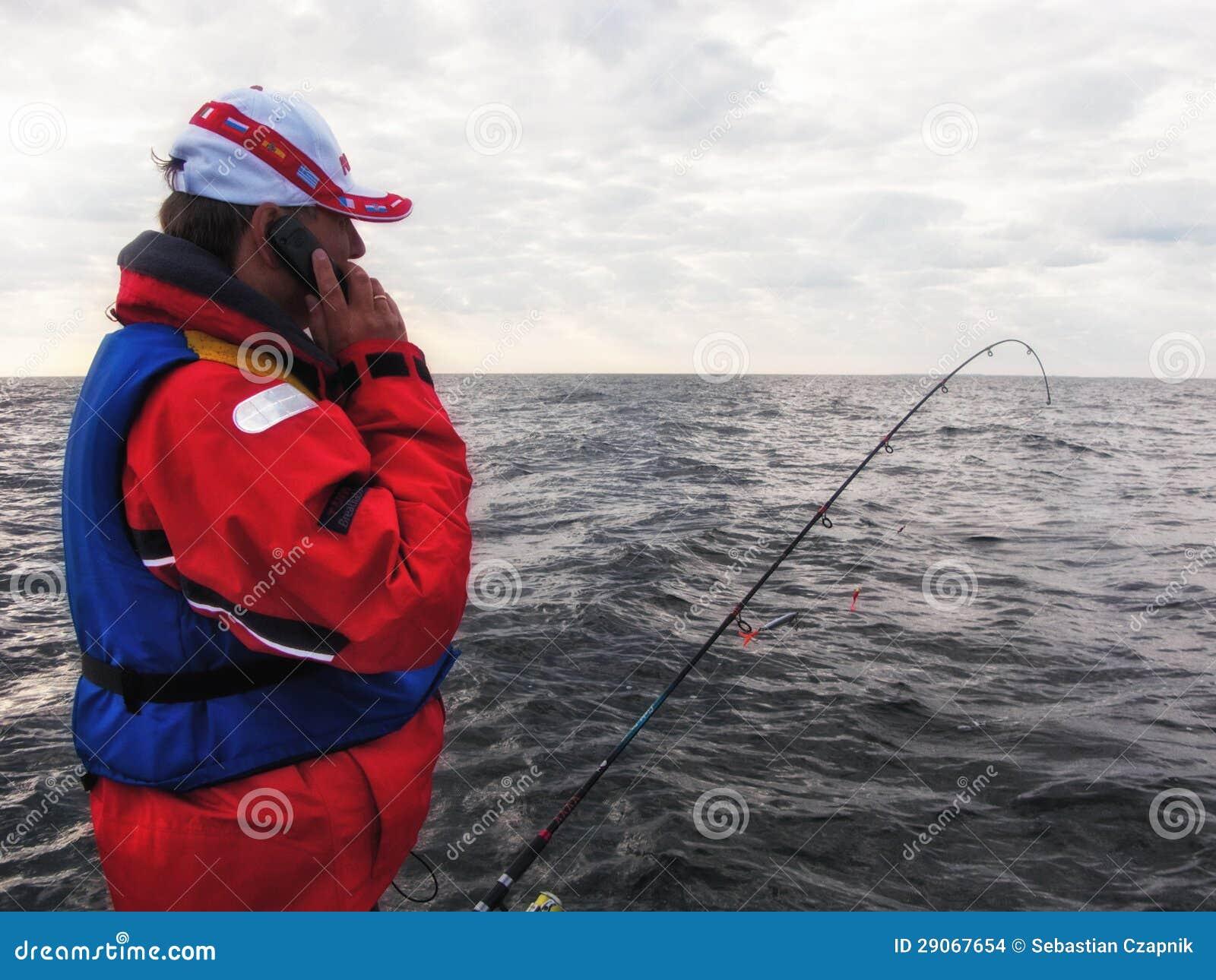 Pescador com telefone móvel