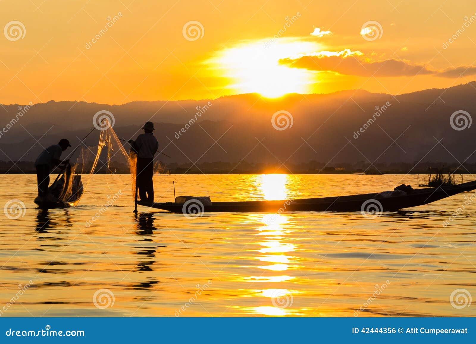 Pescador con el rowing de la pierna durante puesta del sol, lago del inle en Myanmar (