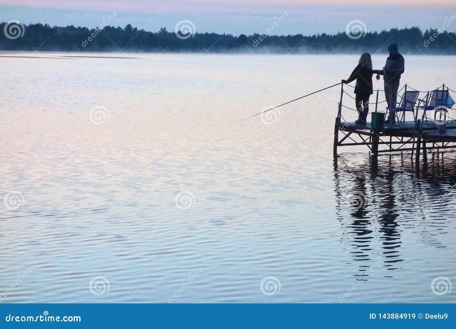 Pescador con una muchacha que pesca en un lago en la puesta del sol