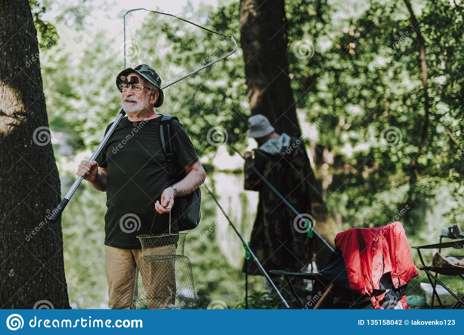 Pescador de sexo masculino positivo que sostiene el equipo de pesca profesional