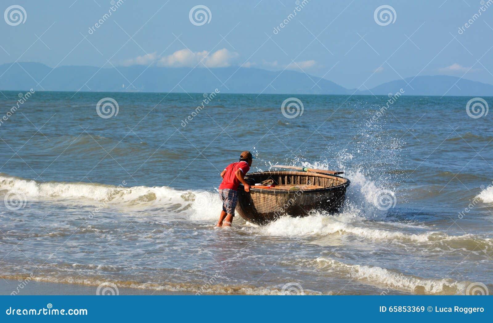 Pescador e seu barco redondo tradicional ( tung chai) Uma praia do golpe Ponto do interst em Vietnam vietnam