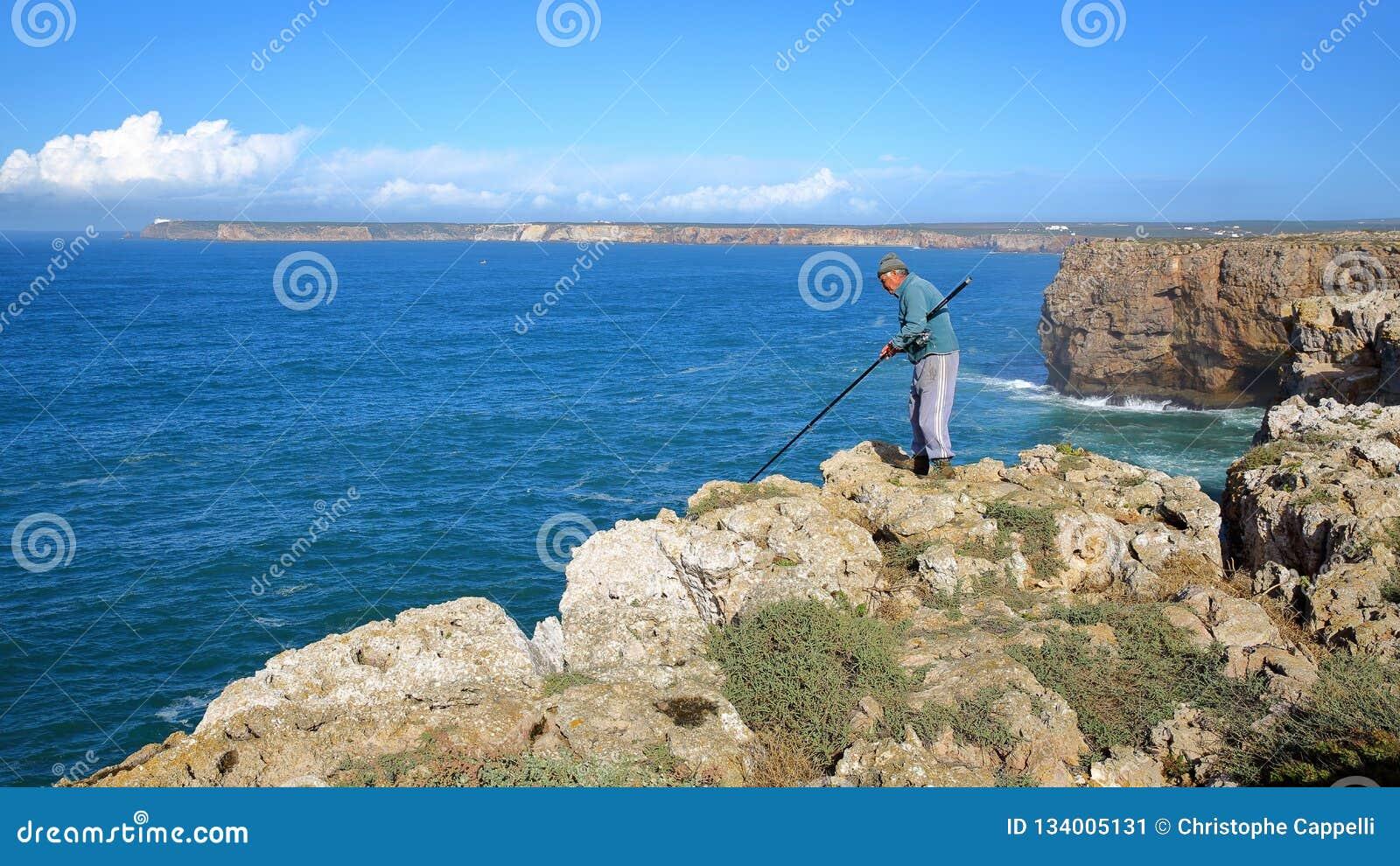 Pescador que dobra acima dos penhascos altos na fortaleza Fortaleza de Sagres com o farol de Cabo de Sao Vicente no fundo
