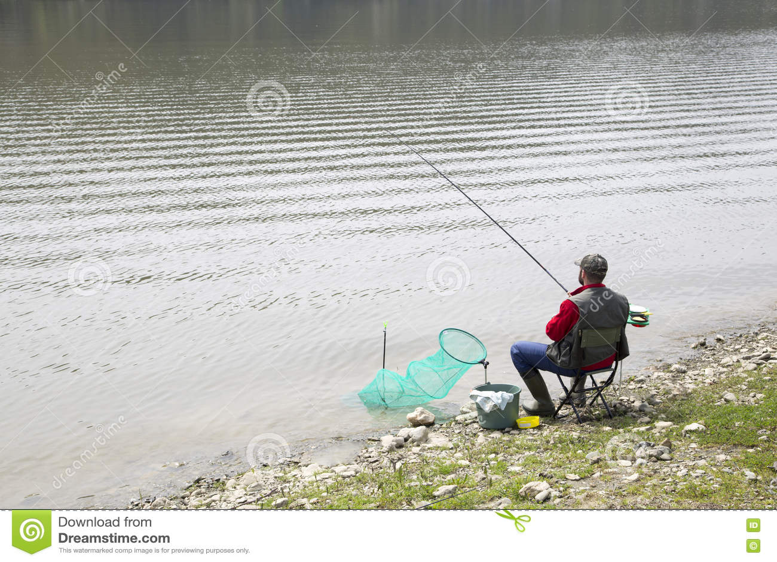 Pescador que se sienta en la costa del río y para los pescados pacientemente que esperan para tomar un cebo