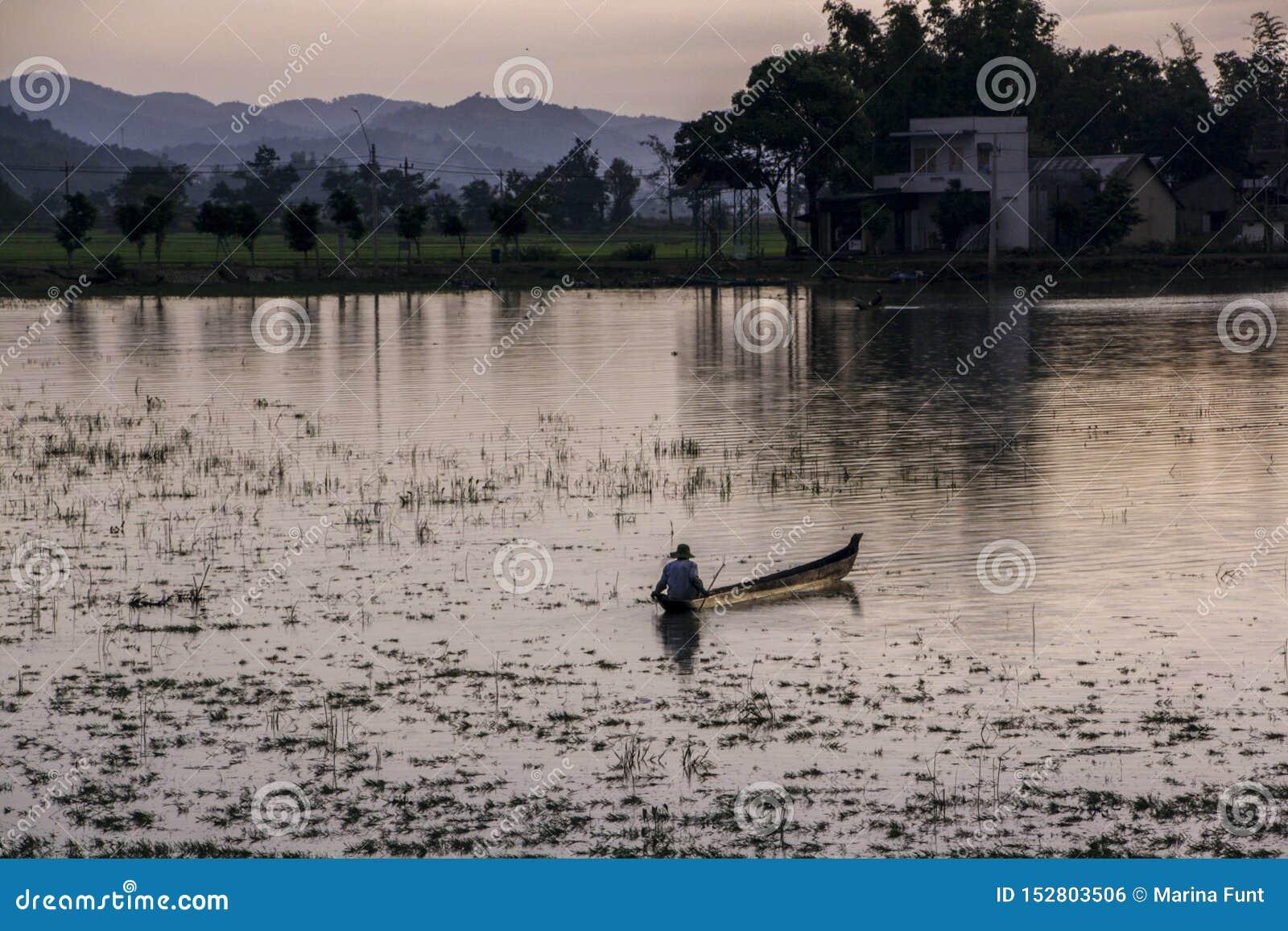 Pescador vietnamita en la navegación de la puesta del sol en un barco a lo largo de la orilla