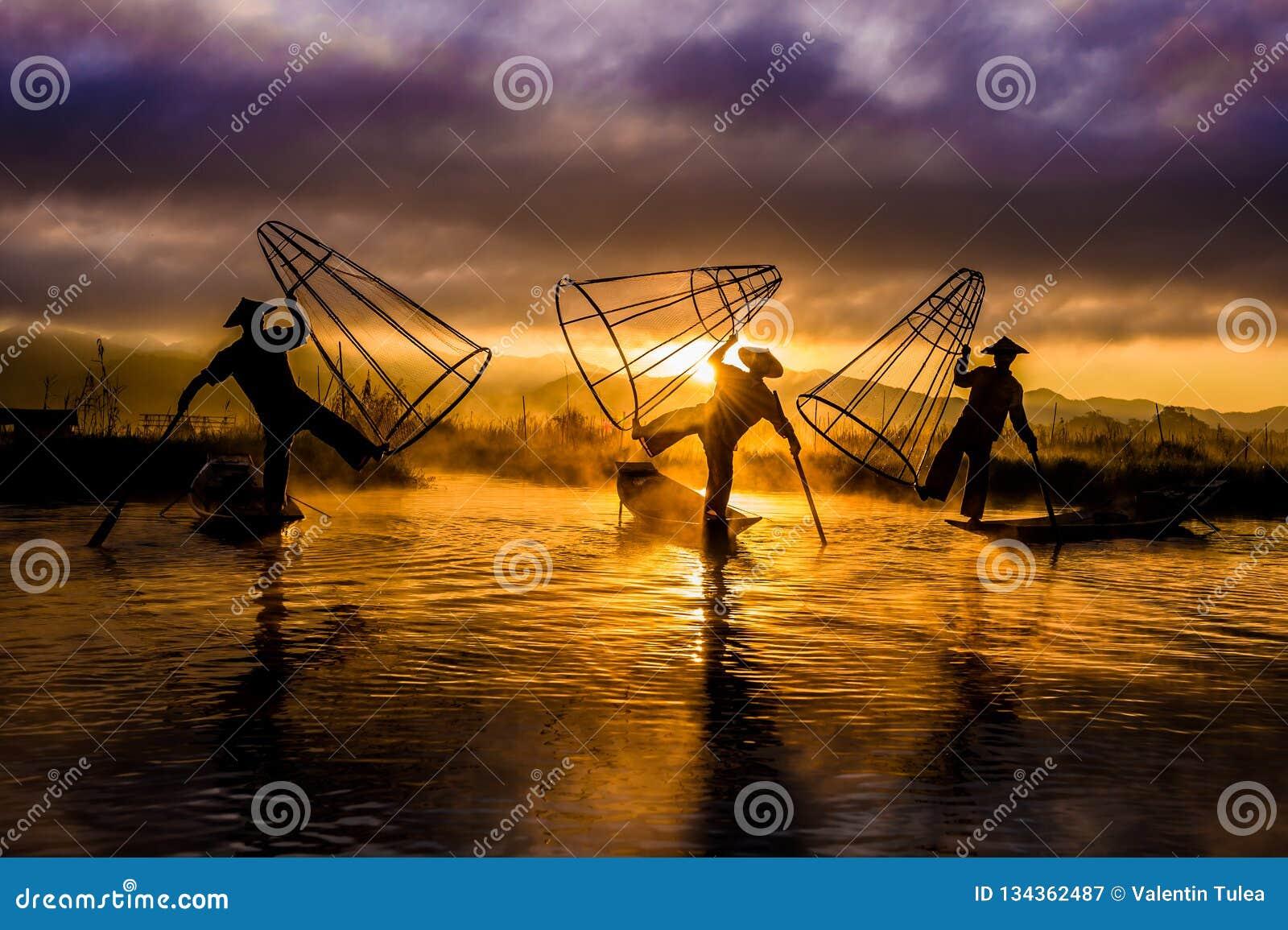 Pescadores Pescadores en el lago Inle en la salida del sol