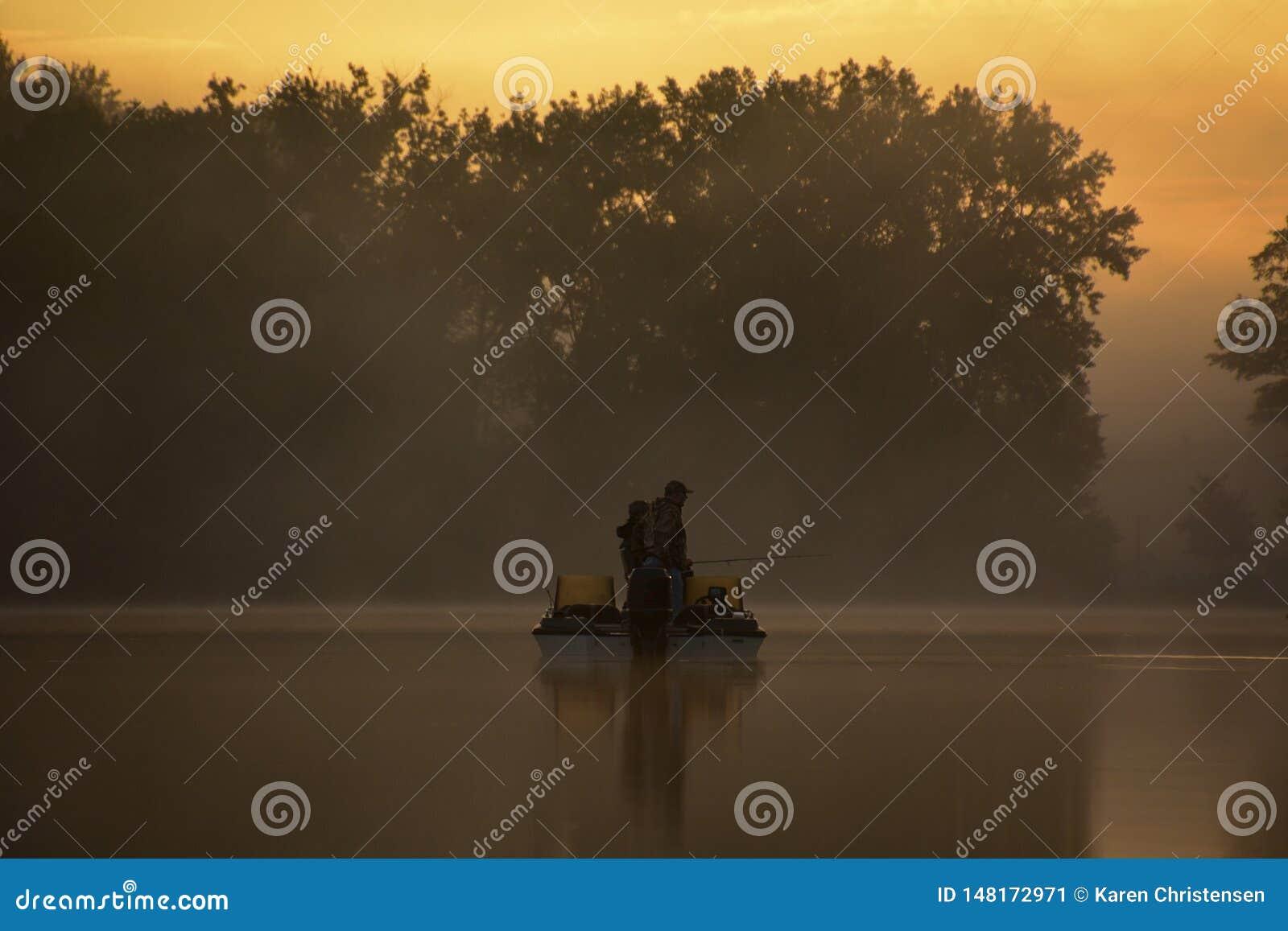 Pescadores na névoa da manhã