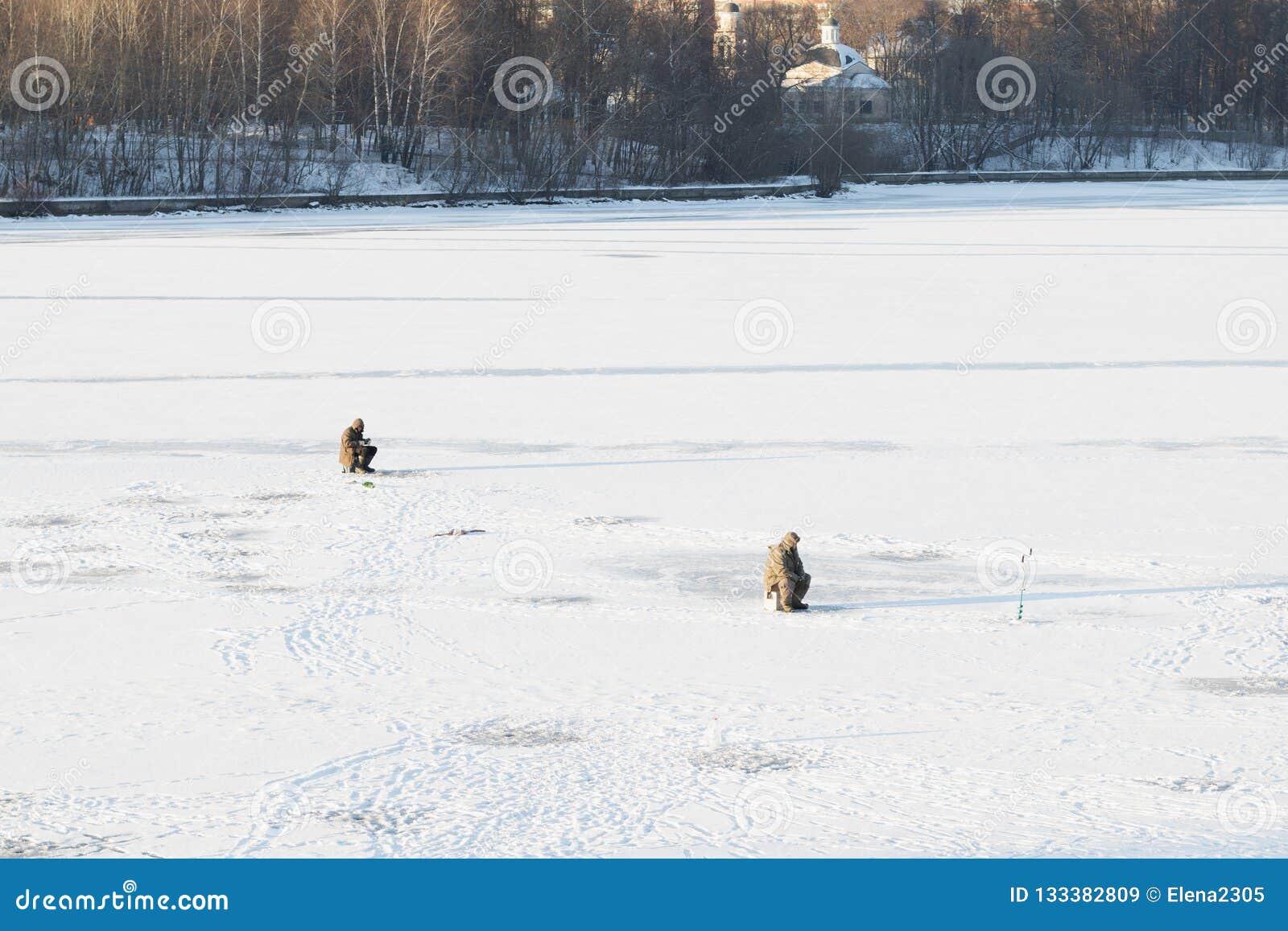 Pescadores no gelo nevado no rio