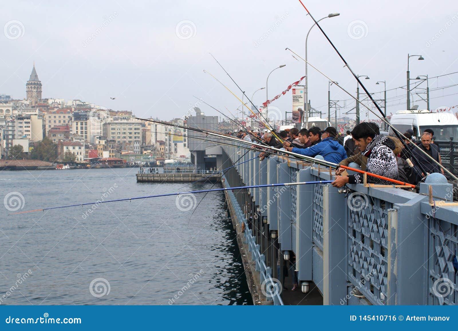 Pescadores que pescam no dia na ba?a dourada do chifre
