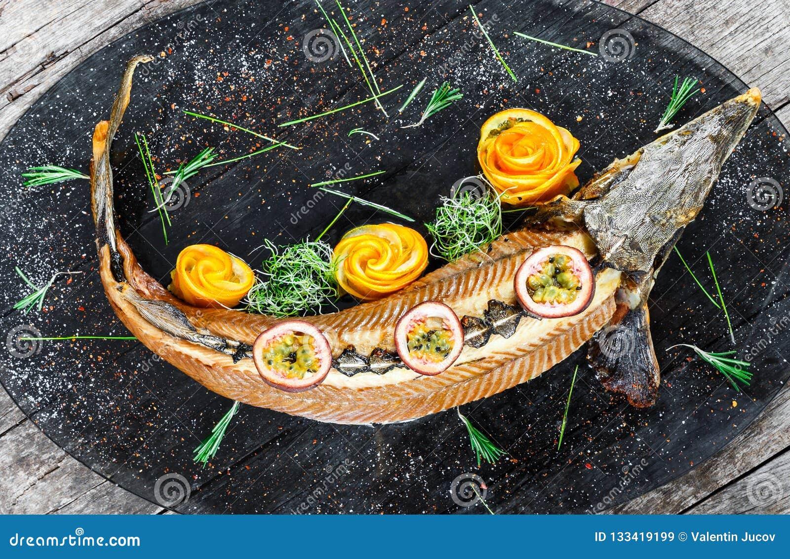 Pescados cocidos del esturión con romero, el limón y la fruta de la pasión en la placa en cierre de madera del fondo para arriba