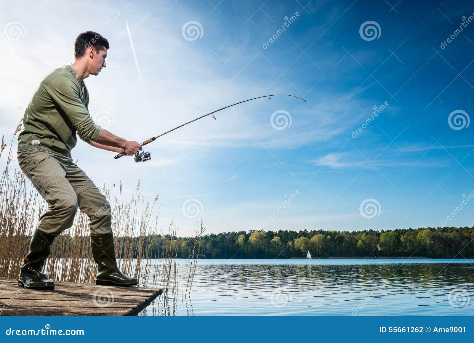 Pescados de cogida del pescador que pescan con caña en el lago