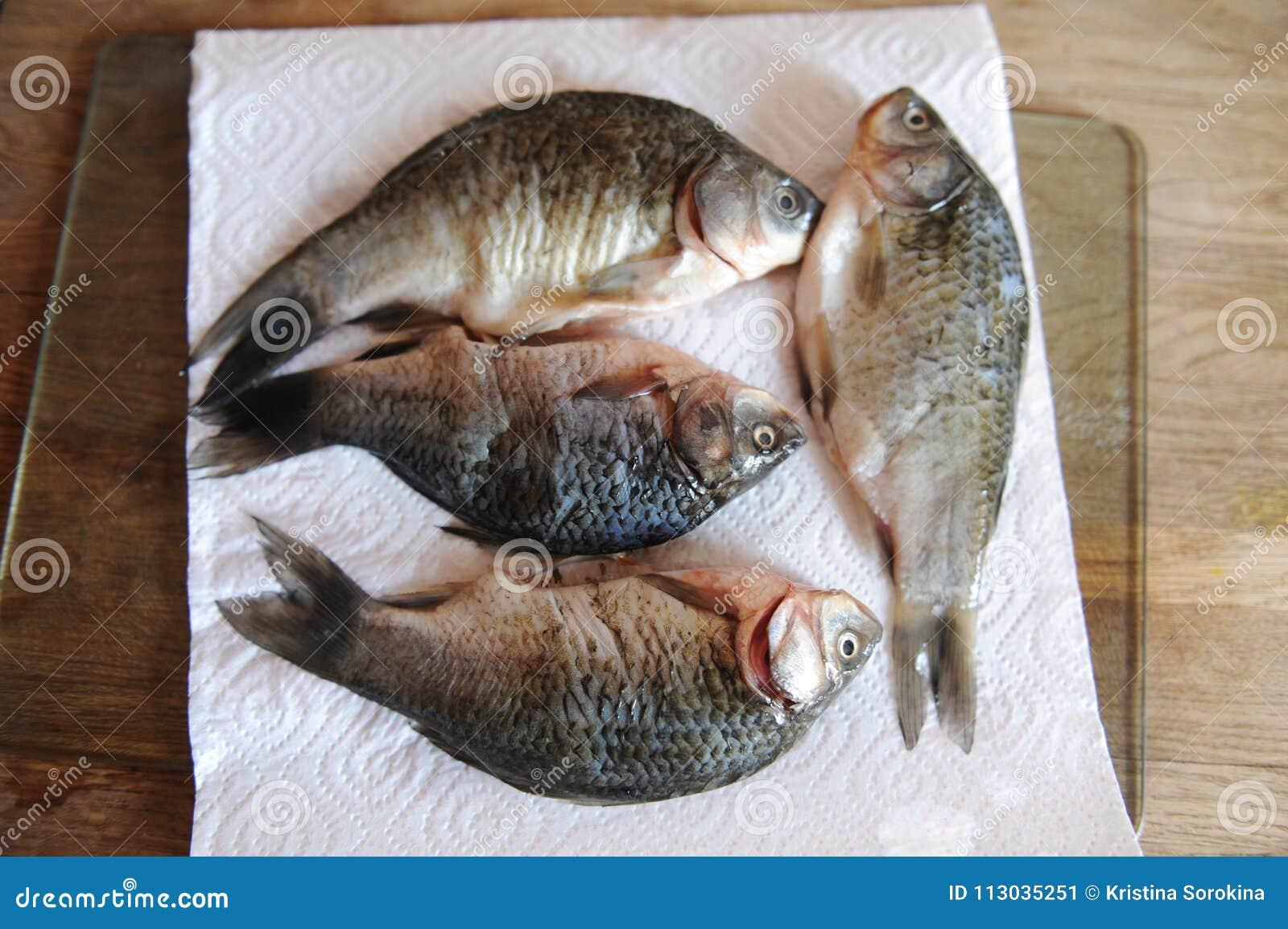Pescados frescos crudos enteros en tablero cortado El proceso de cocinar
