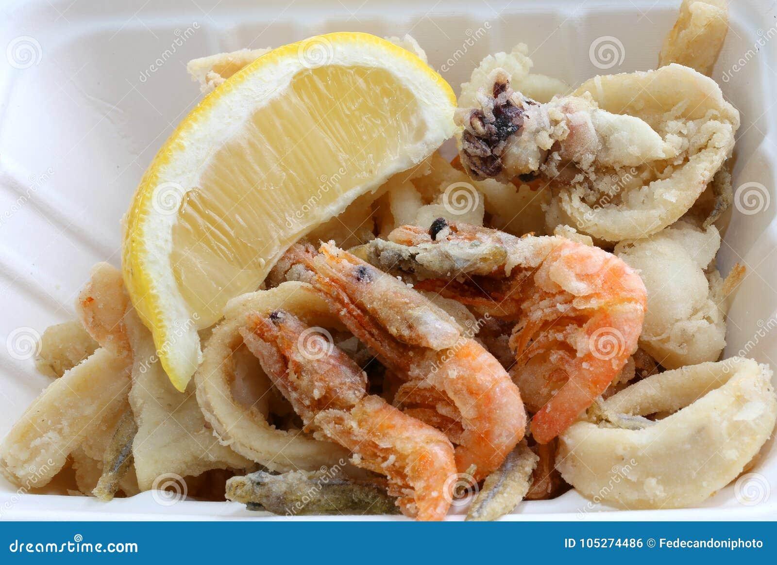 Pescados fritos con el camarón para llevar y una rebanada de limón