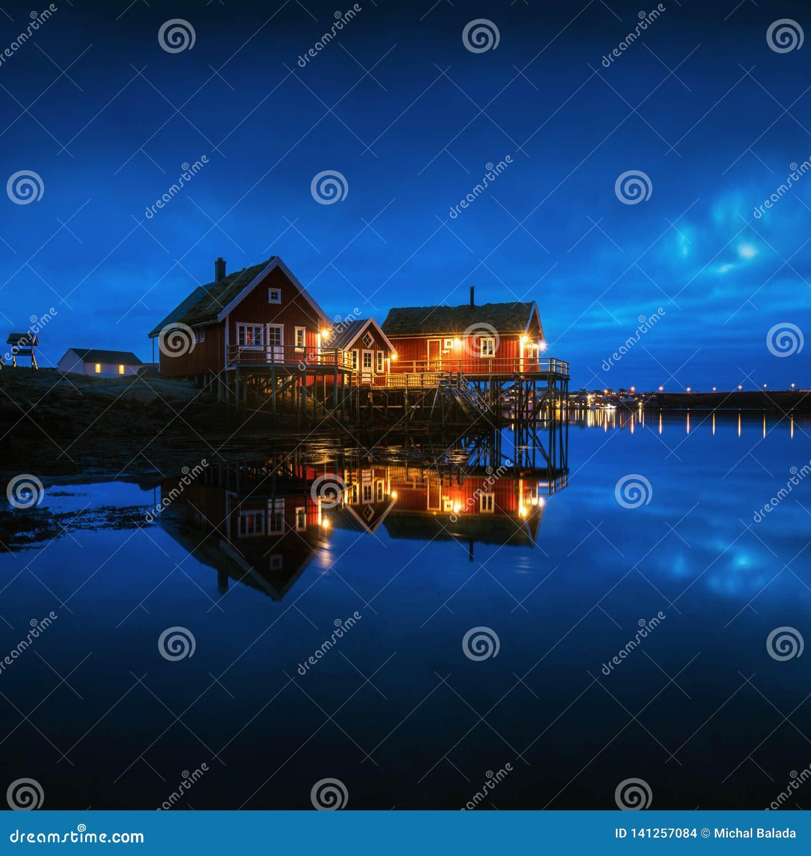 Pescando reflexões de Reine da cidade na noite em ilhas de Lofoten em Noruega, acima da paisagem do inverno do círculo ártico com
