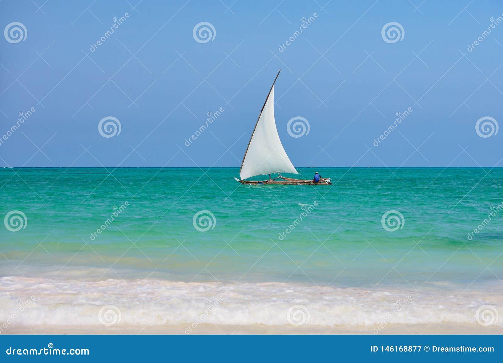 Pescatore che si siede in crogiolo di dhow che naviga le acque blu