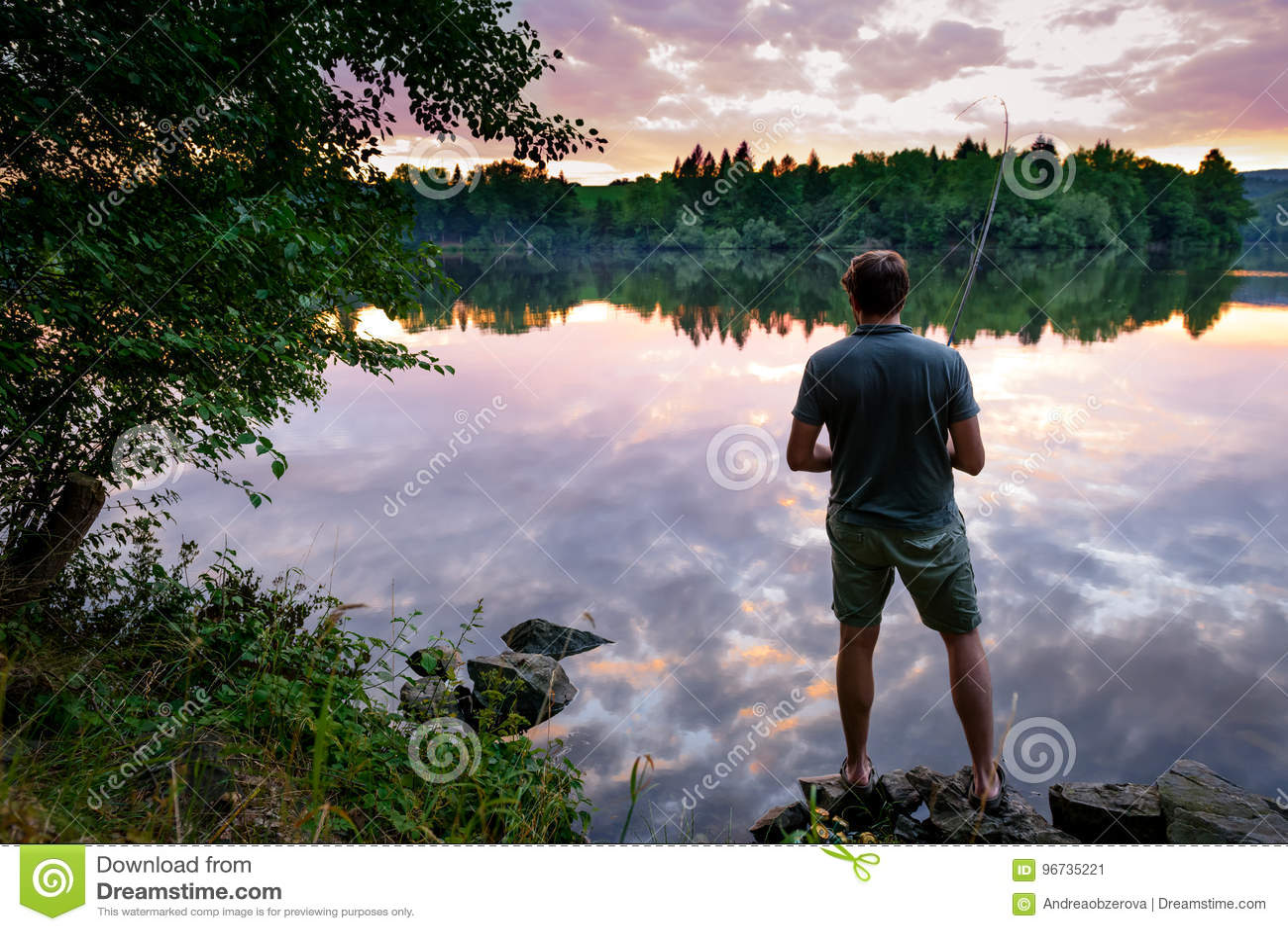 Pescatore che sta sulle banche della Moldava al bello tramonto, da pesca concetto