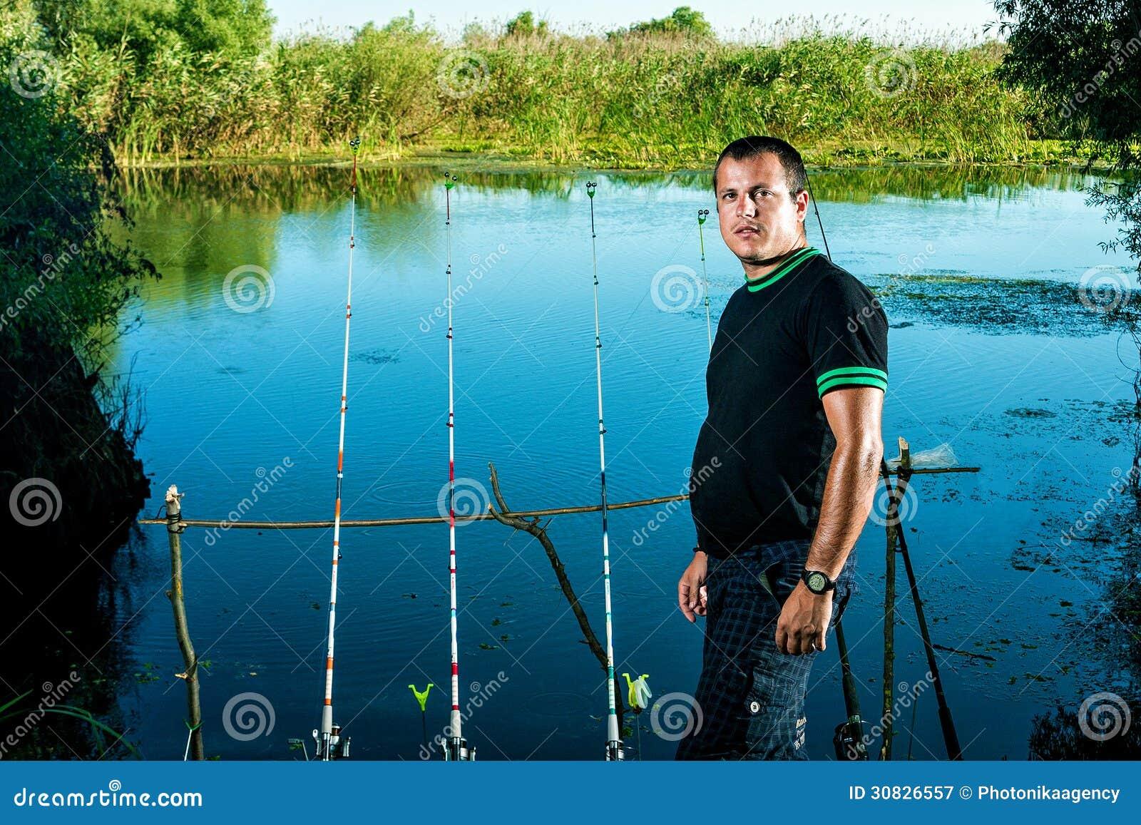 Pescatore su un lago con le canne da pesca