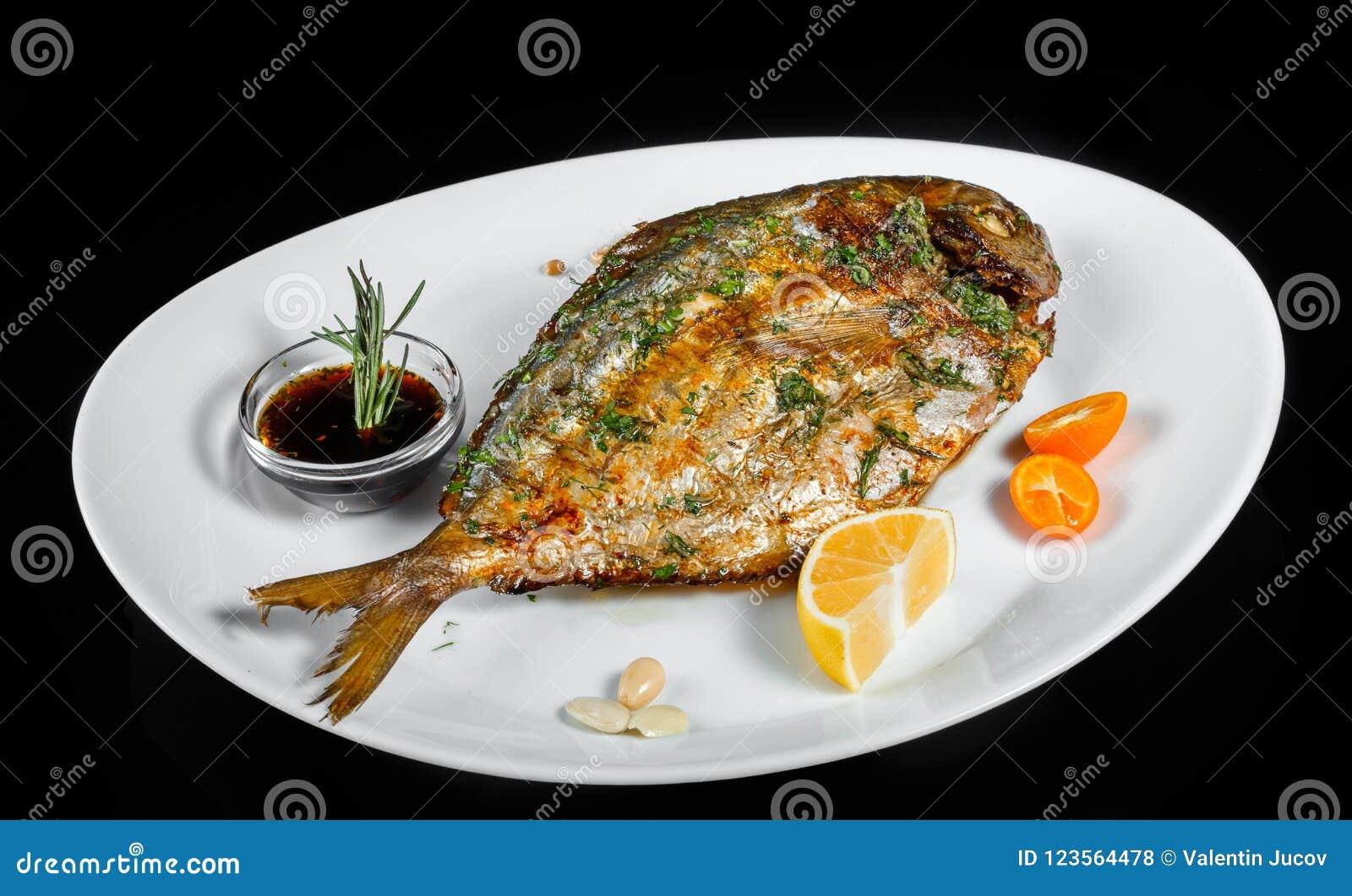 Pesce arrostito di dorado con i verdi e limone su fondo nero isolato