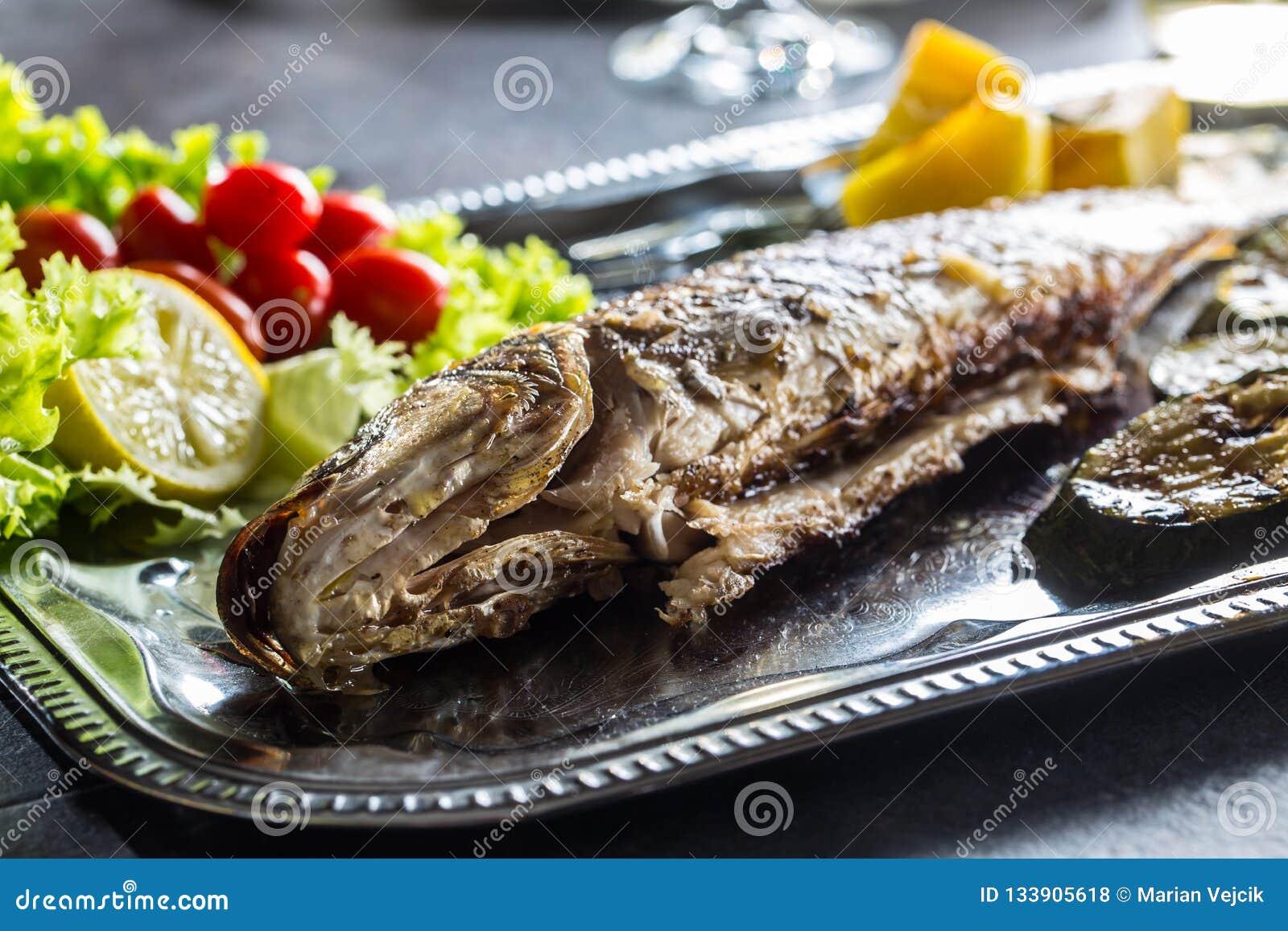 Pesce arrostito sul piatto con la verdura fresca e arrostita