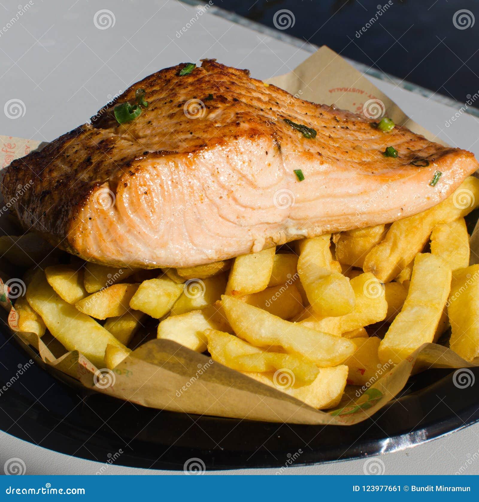 Pesce di color salmone arrostito con le patate fritte su un piatto di plastica nero