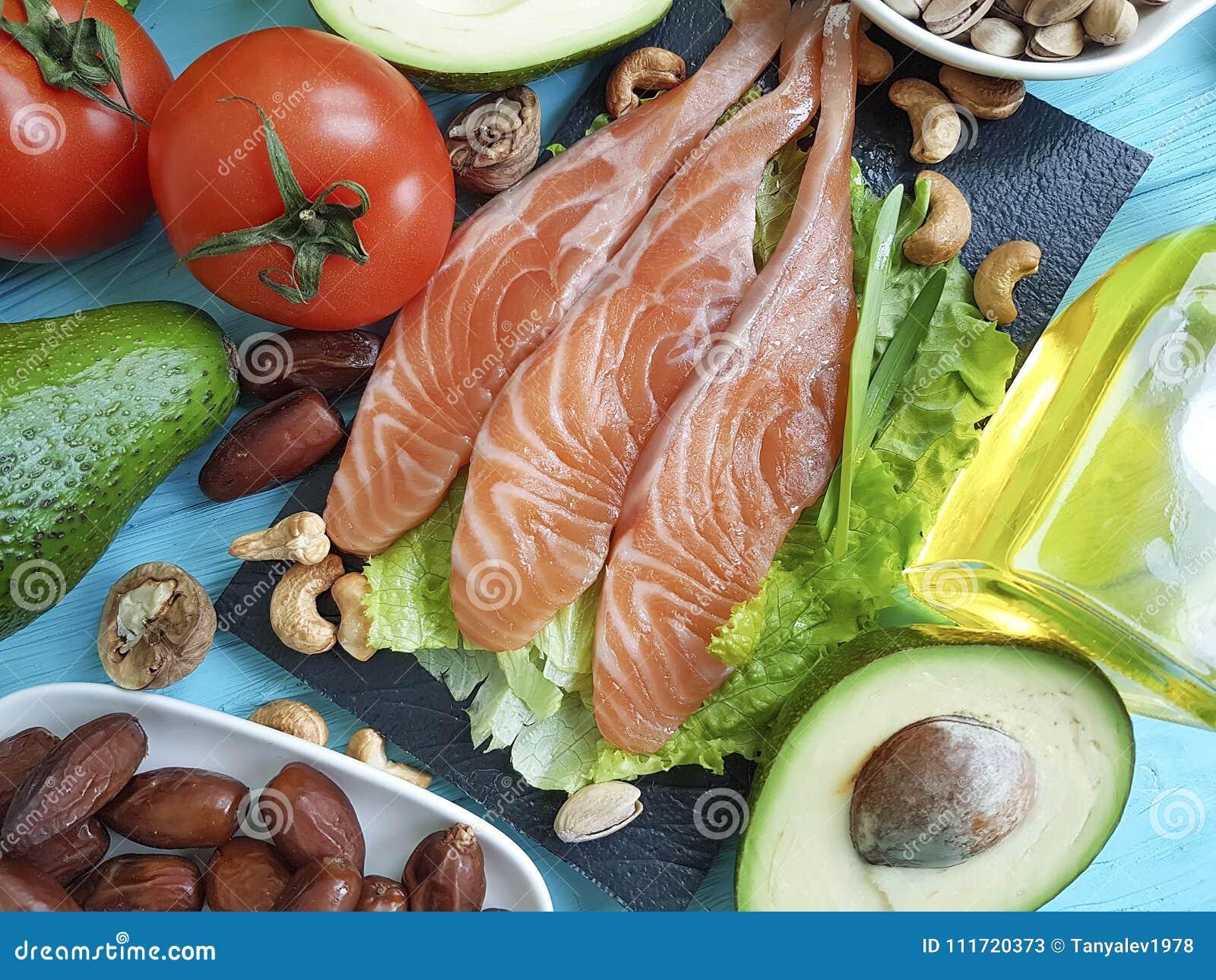 Peschi l avocado di color salmone di Omega 3 di alimentazione dell insalata sull alimento sano del fondo di legno blu