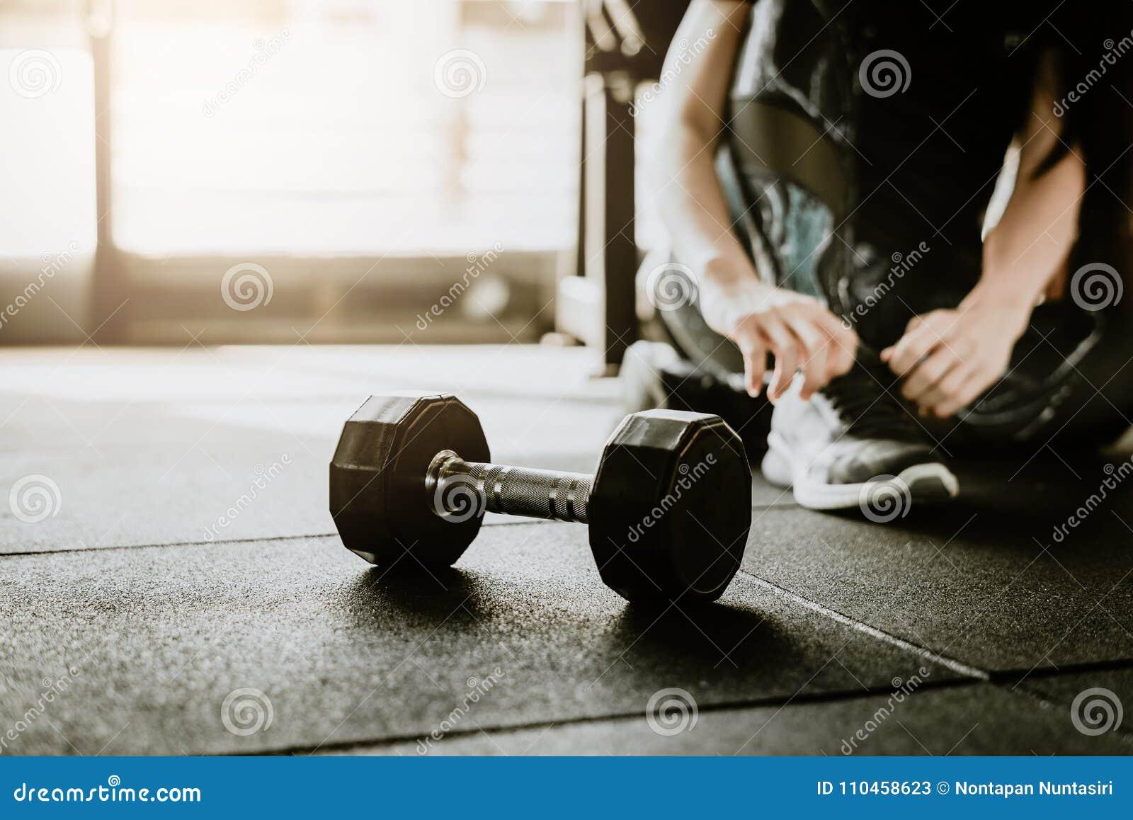 Peso no assoalho no gym com a mulher no fundo