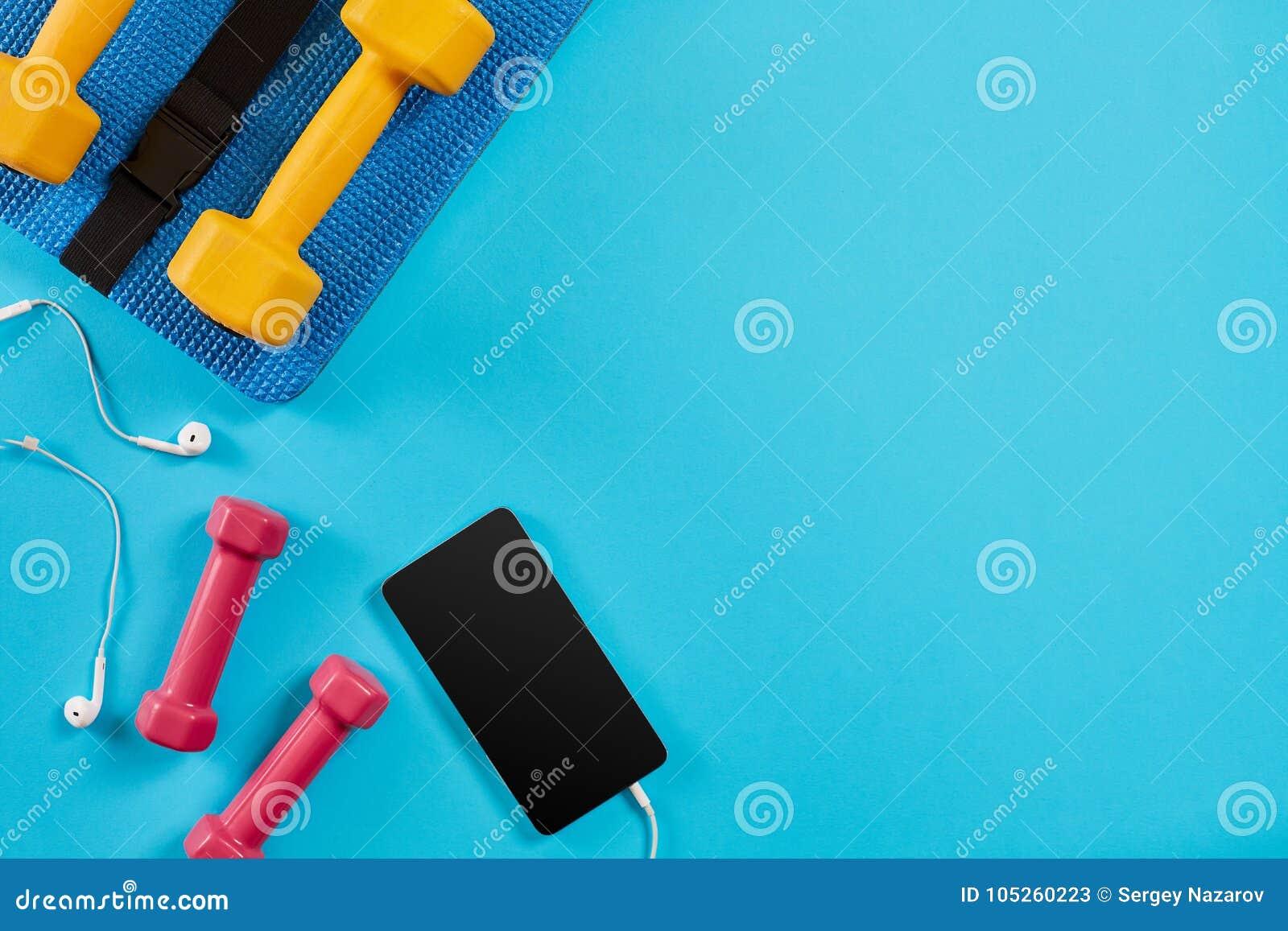 Pesos e telefone celular no fundo azul Vista superior Aptidão, esporte e conceito saudável do estilo de vida