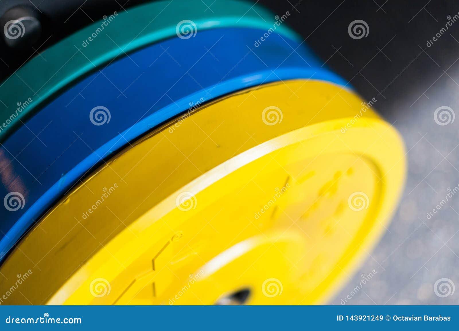 Pesos pesados coloreados de la pesa de gimnasia en gimnasio