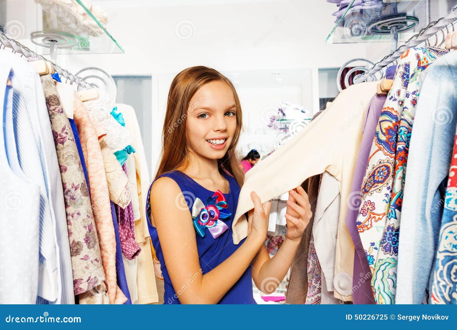 48002dbbc Menina feliz entre a roupa nos ganchos e a pesquisa pela roupa na loja