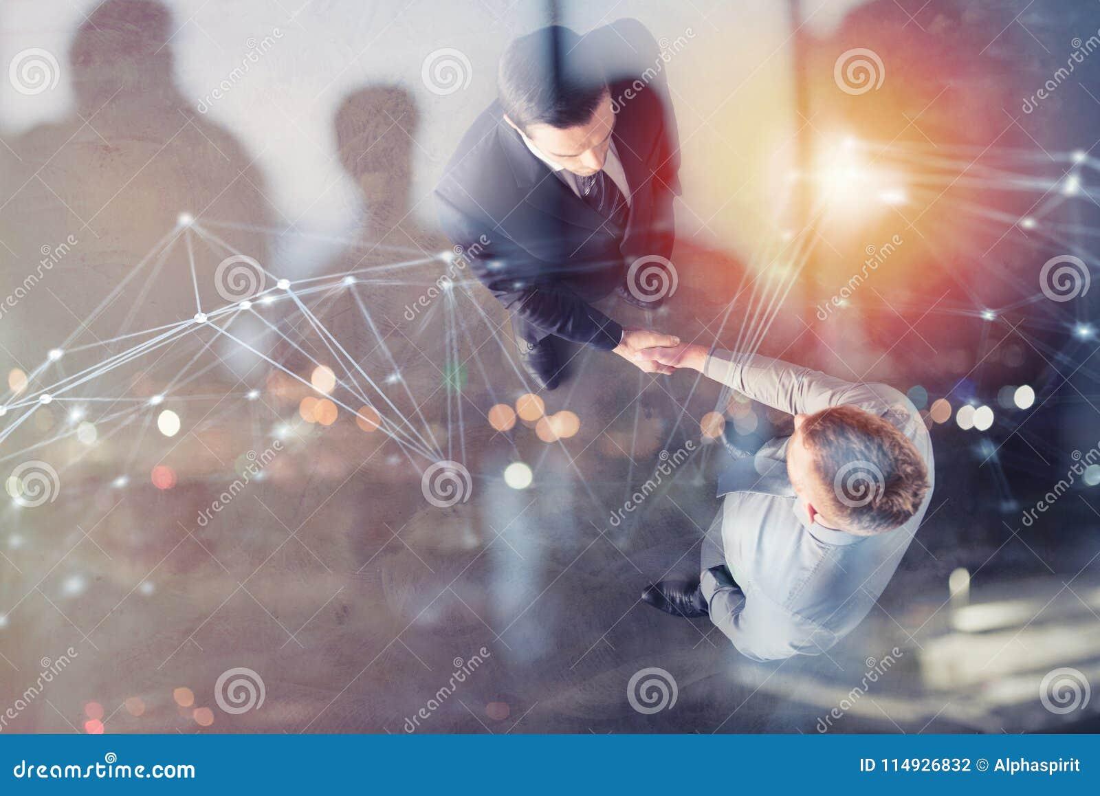 Pessoa do negócio do aperto de mão no escritório com efeito da rede Conceito dos trabalhos de equipa e da parceria Exposição dobr