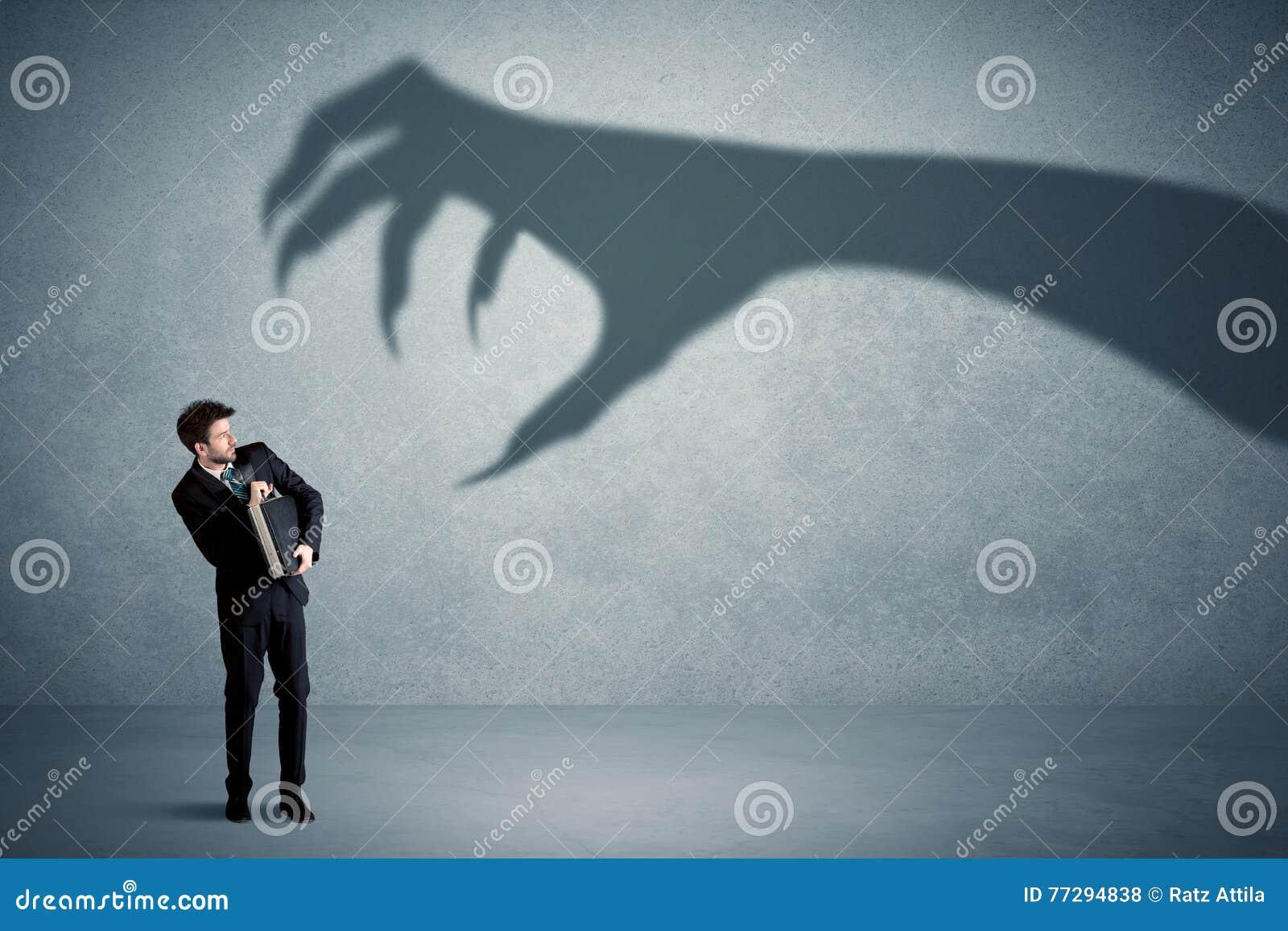 Pessoa do negócio receosa de um conceito grande da sombra da garra do monstro