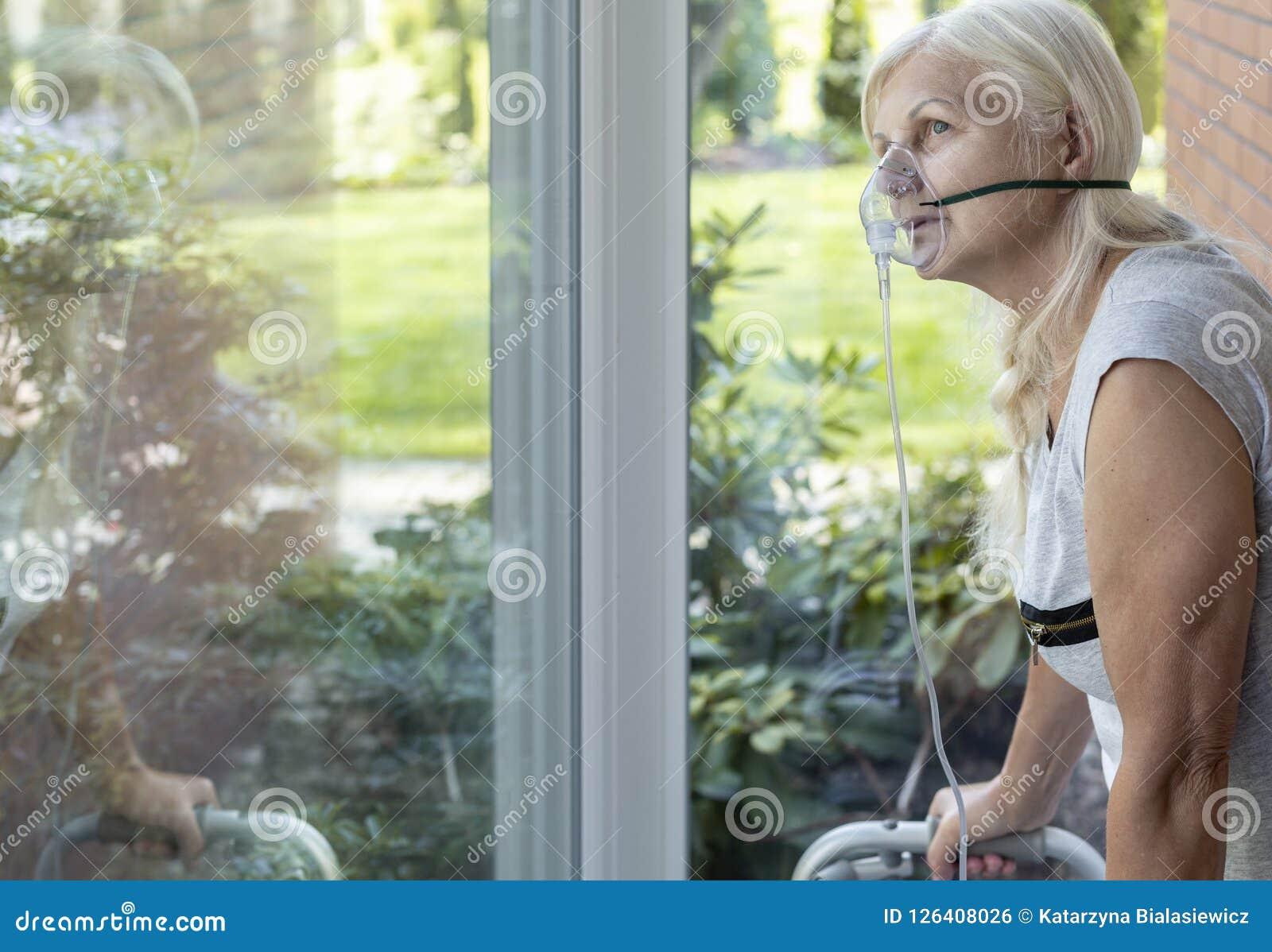 Pessoa mais idosa com uma máscara de respiração do oxigênio que olha uma janela