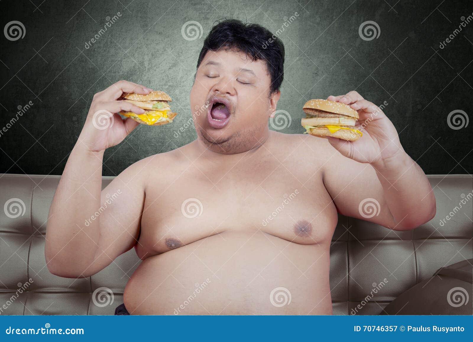 A pessoa obeso come o cheeseburger no sofá