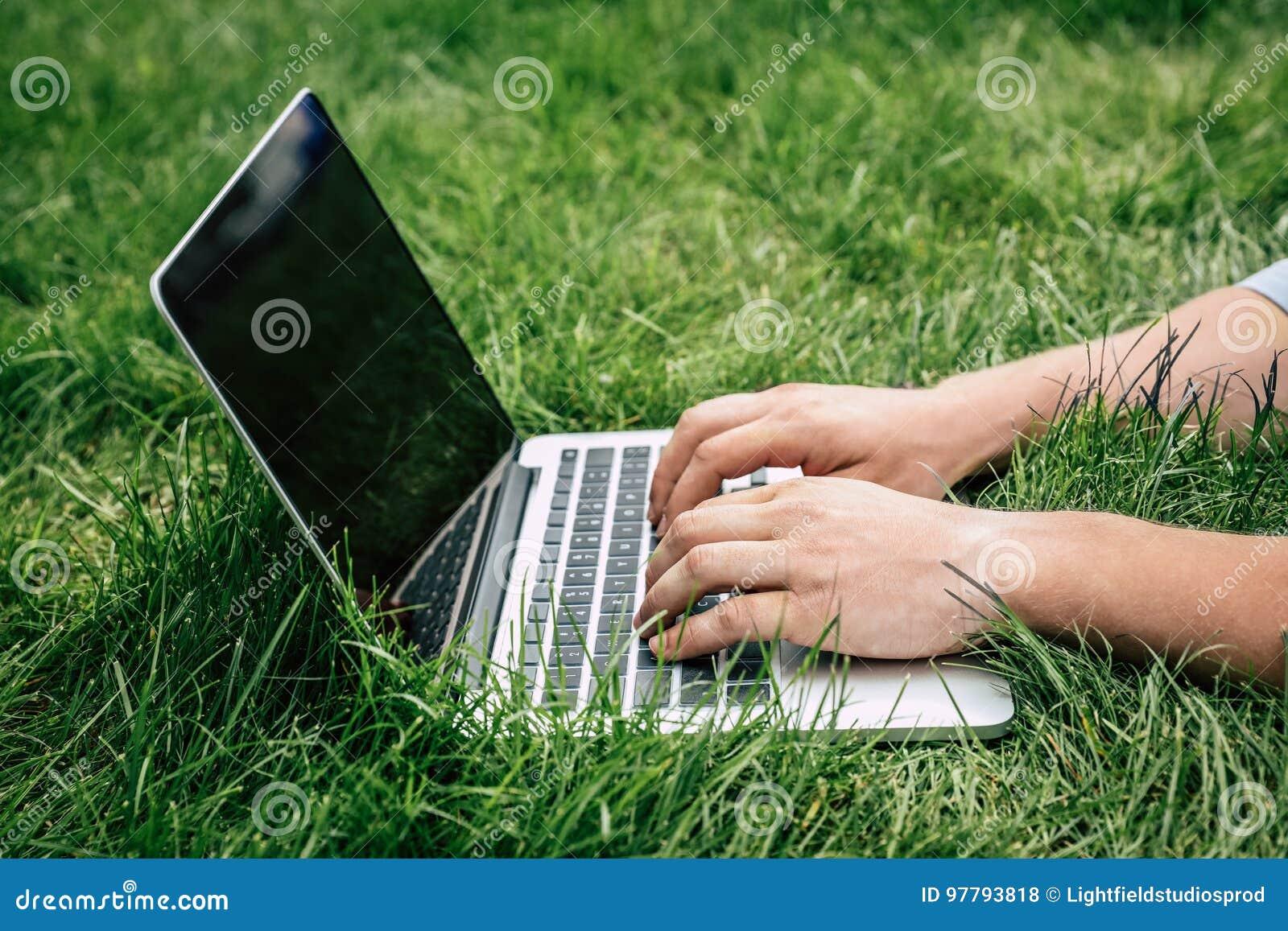 Pessoa que datilografa no portátil com tela vazia fora