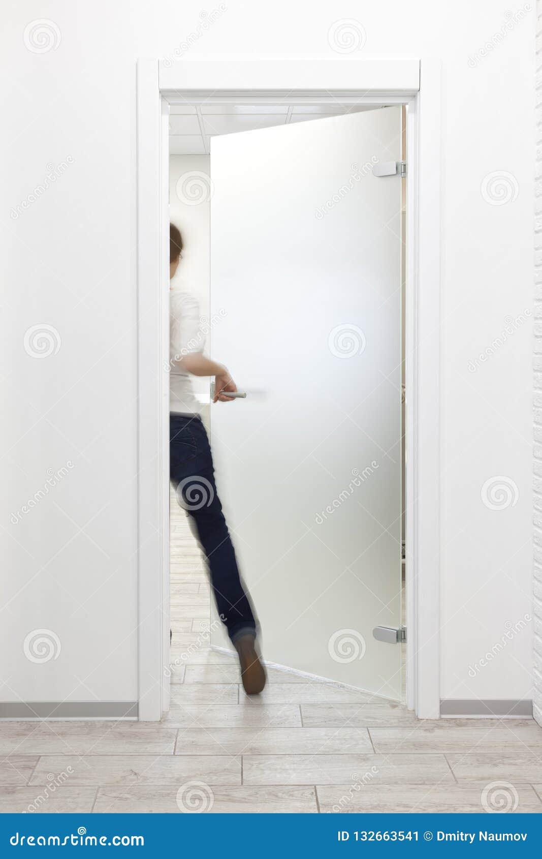 Pessoa que entra em uma sala no escritório com interior branco minimalista