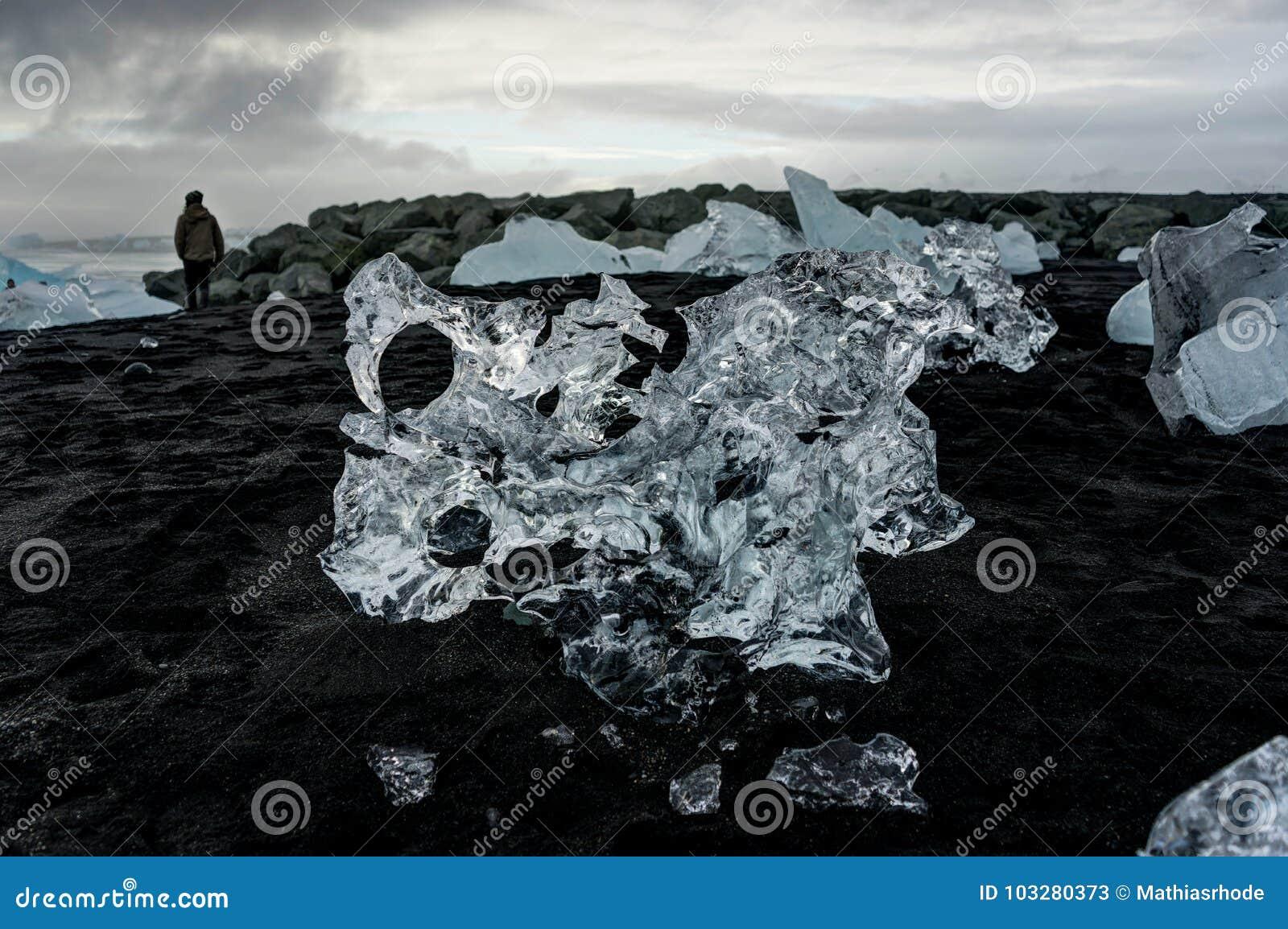 Pessoa que está na praia preta com os iceberg que flutuam em Jokulsa