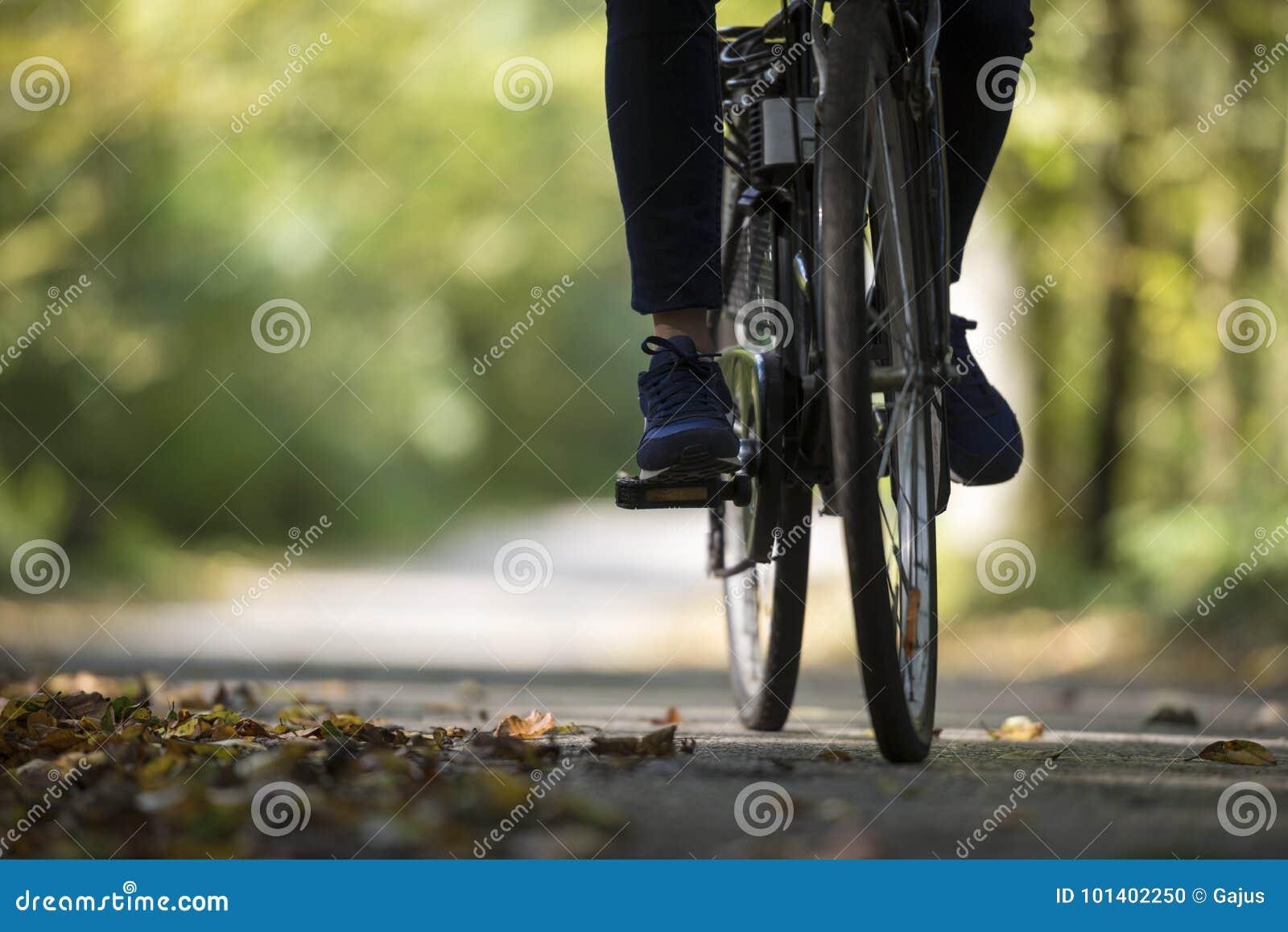 Pessoa que monta uma bicicleta ao longo de uma estrada da queda