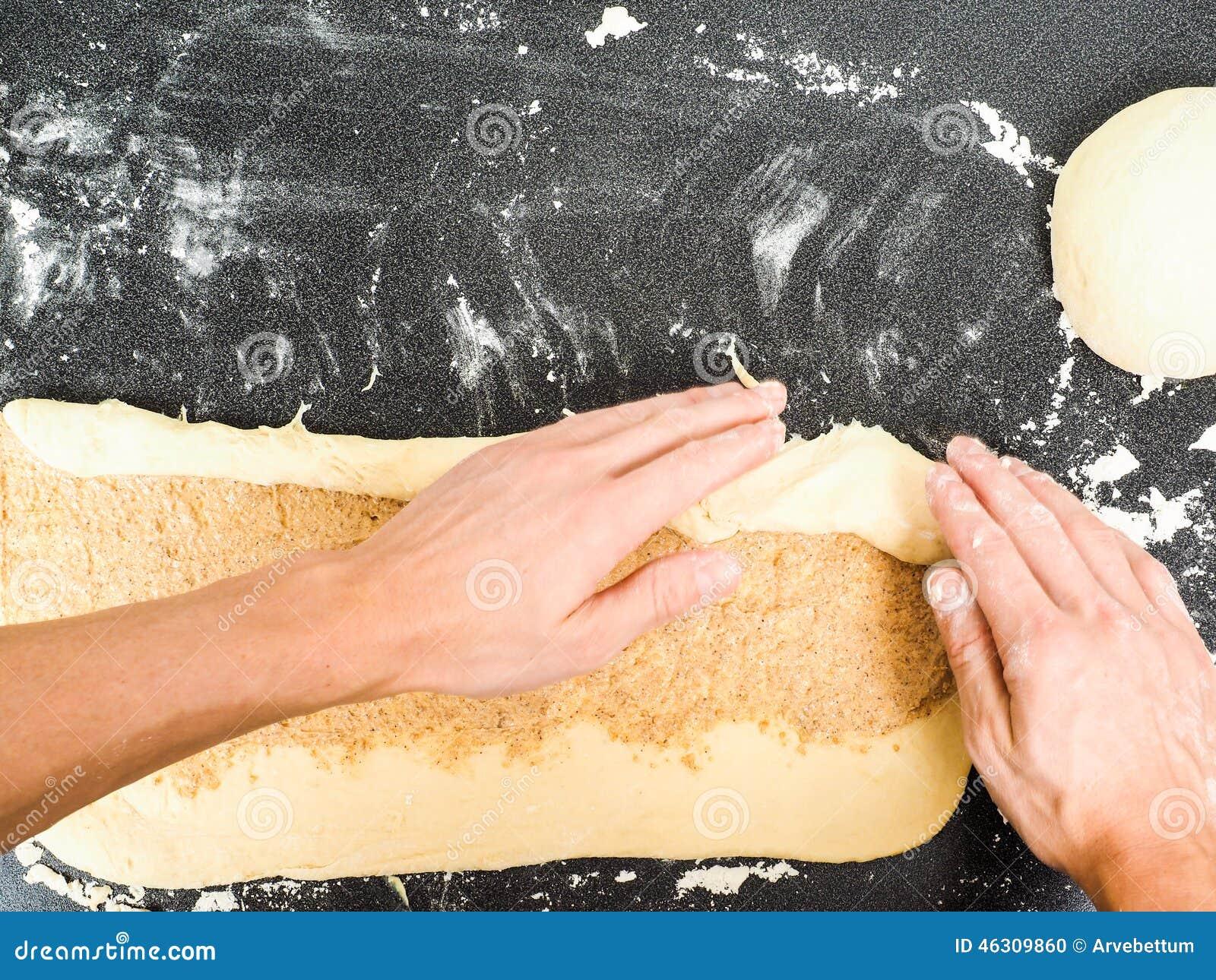 Pessoa que rola um bolo do caracol com propagação
