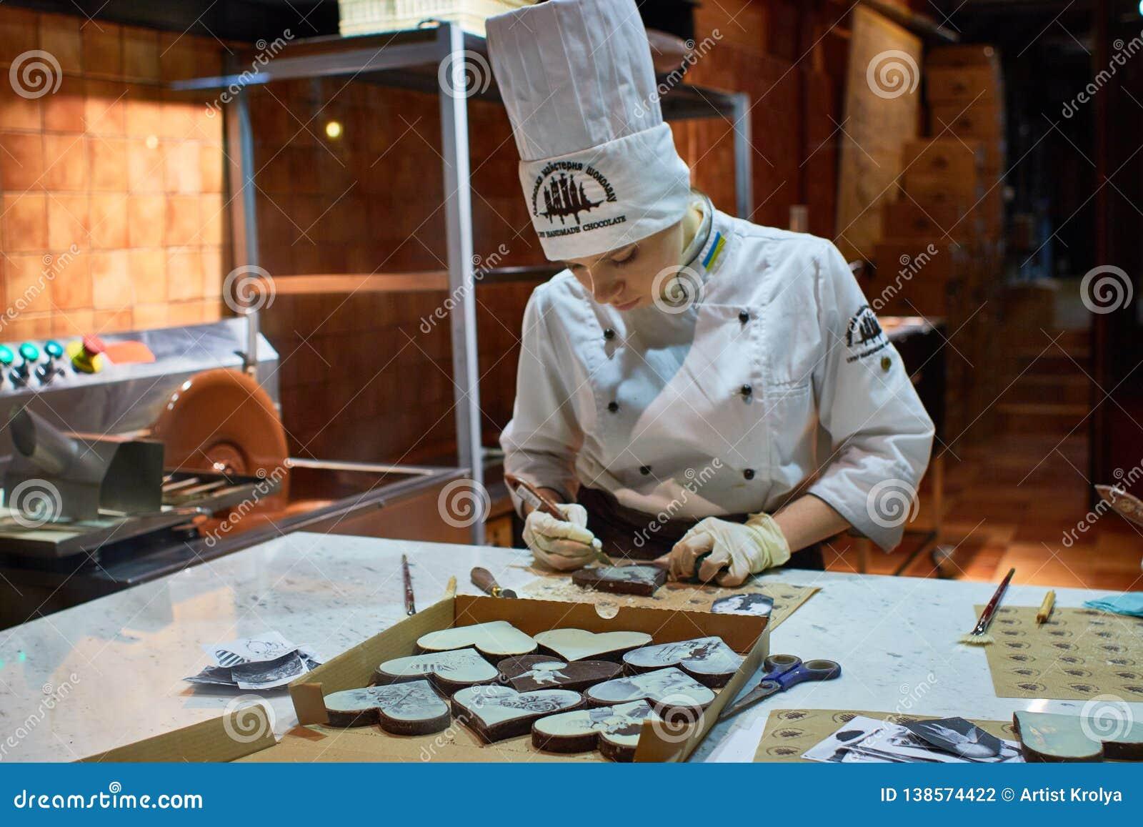 Pessoa que trabalha para dentro da fábrica caseiro do chocolate de Lviv