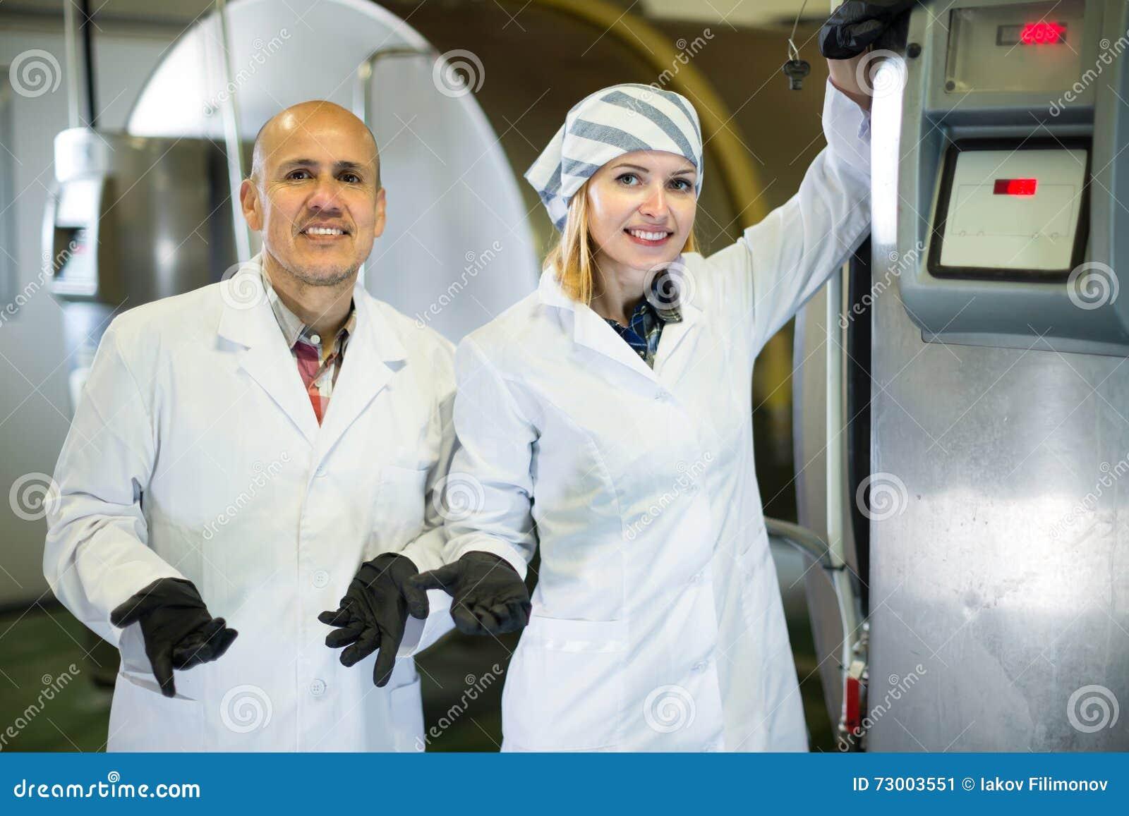 Pessoal da exploração agrícola com os reservatórios do leite na planta