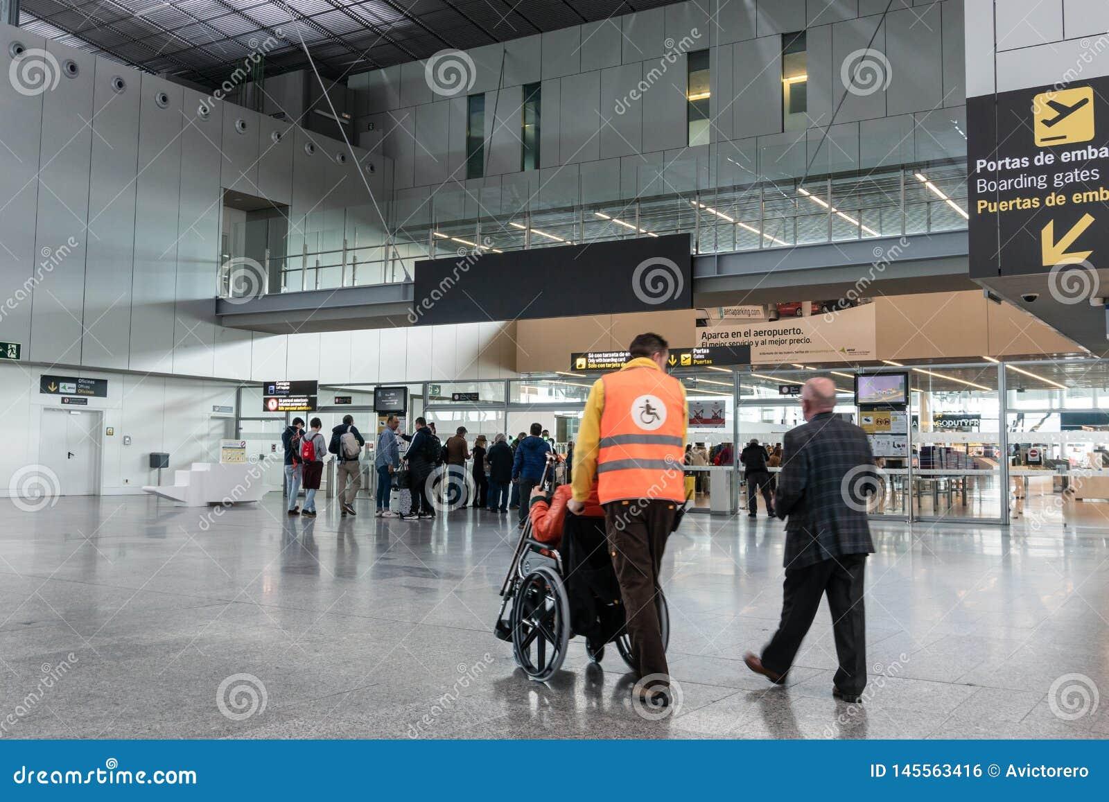 Pessoal do aeroporto que empurra empurrando povos na cadeira de rodas no aeroporto