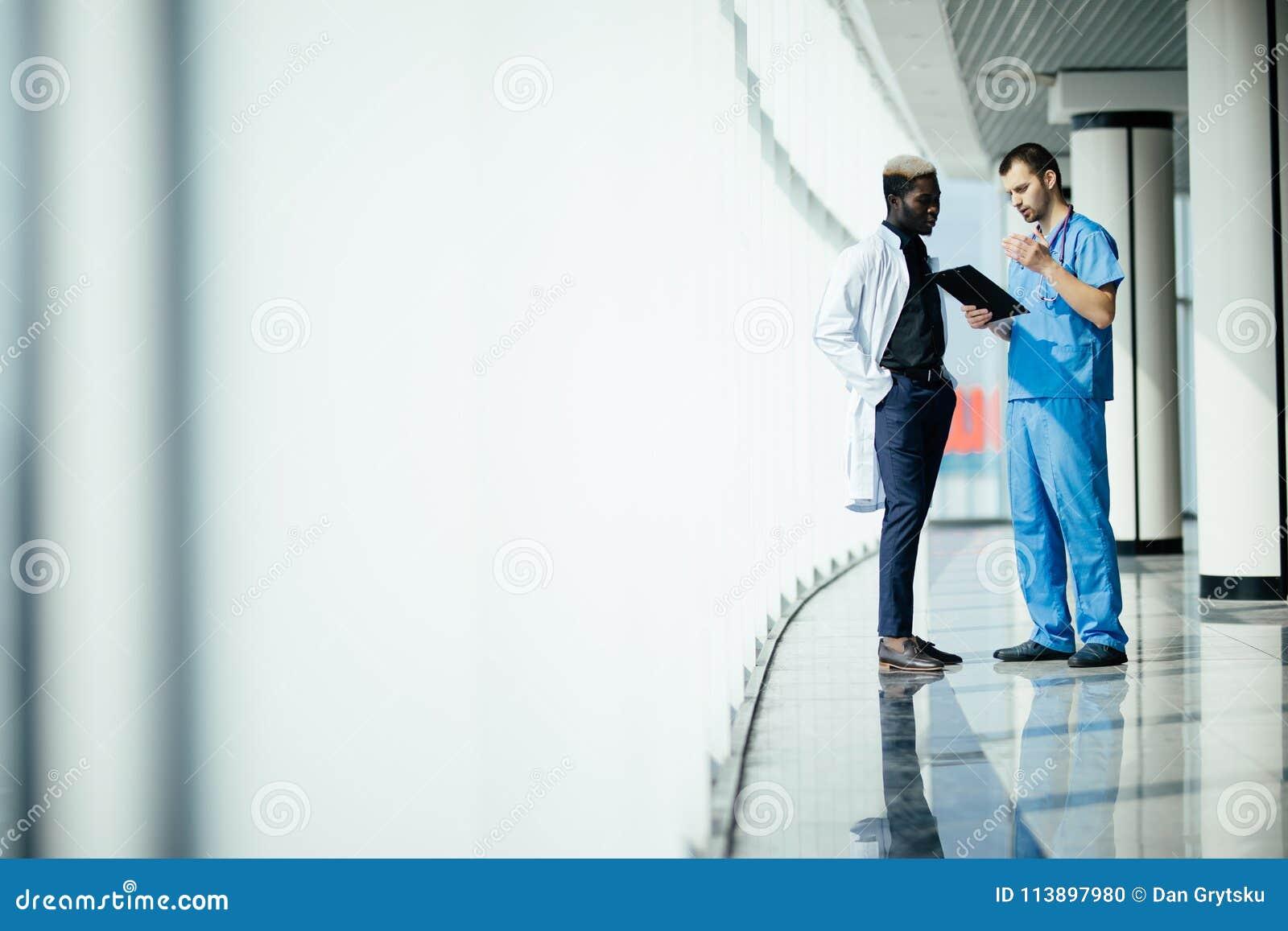 Pessoal multi-étnico médico que tem a discussão em um corredor do hospital Dois doutores que trabalham em uma clínica médica Dois