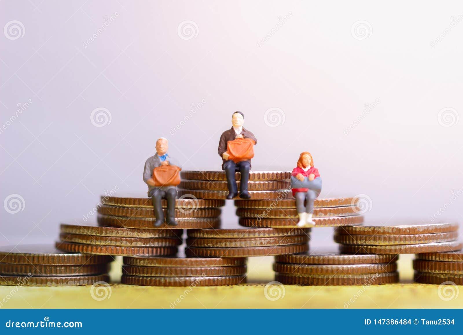 Pessoas adultas que sentam-se na pilha das moedas Planeamento de aposenta??o