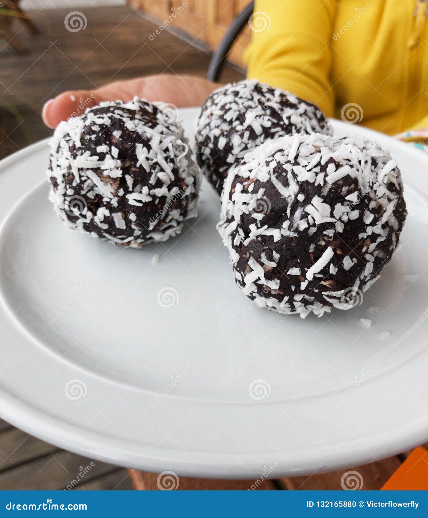 Petisco da época de férias do Natal, sobremesa, doces, deleite, padaria, bolo dos confeitos: Bolas do rum polvilhadas com o coco