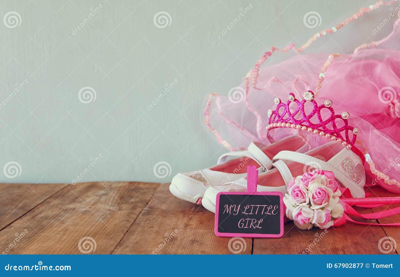 Petit équipement de partie de filles : fleurs blanches de chaussures, de couronne et de baguette magique à côté de petit tableau