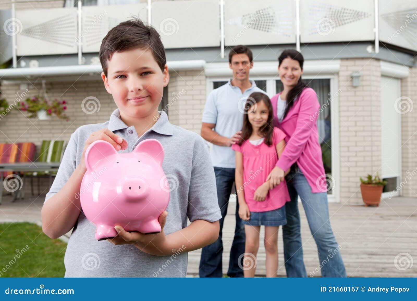 Petit argent d économie de garçon avec la famille au fond