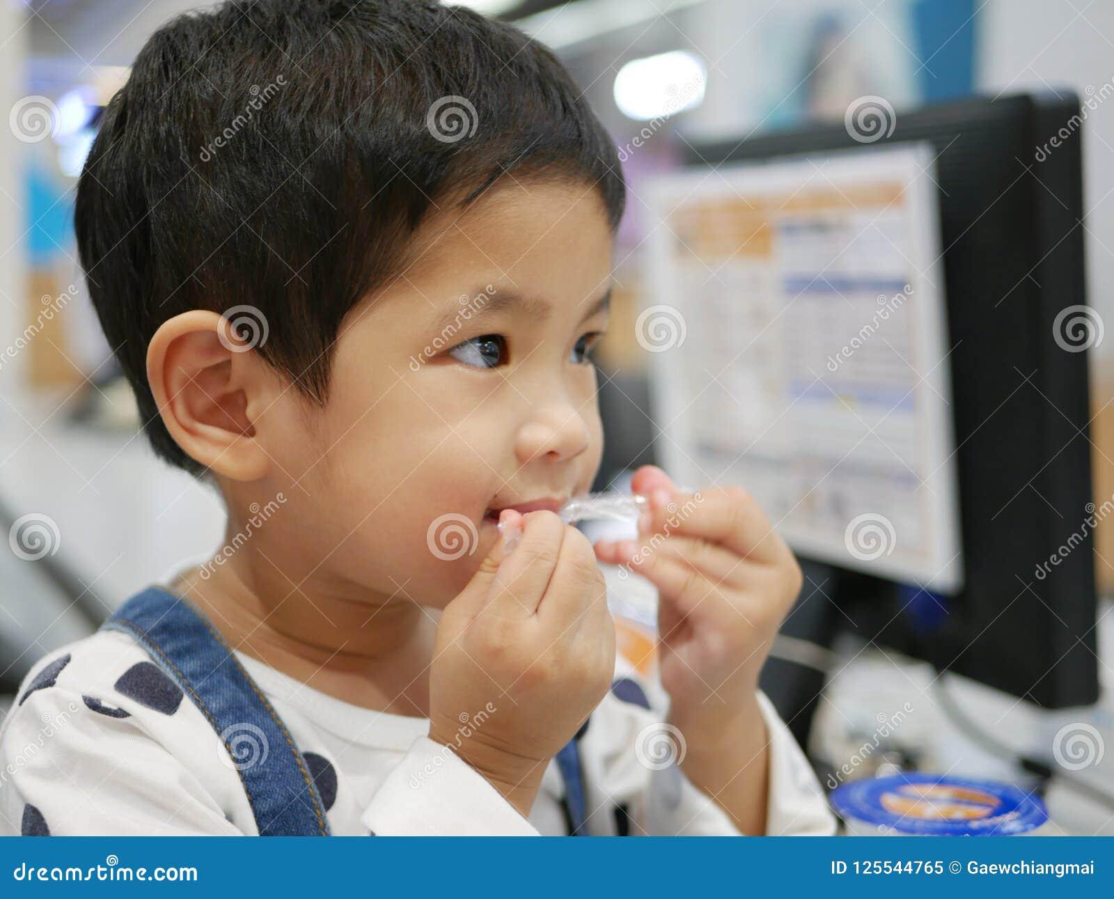 Petit bébé asiatique prenant une paille de son paquet à l aide de ses dents