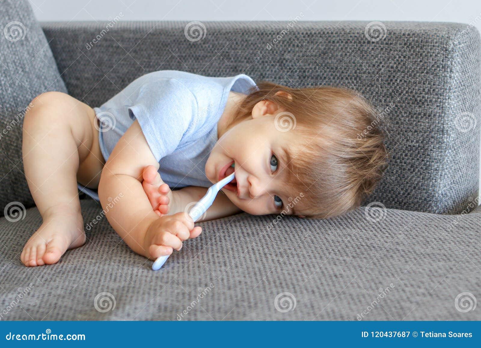 Petit bébé garçon de sourire mignon tenant la brosse à dents dans sa bouche et nettoyant ses premières dents se situant dans la p