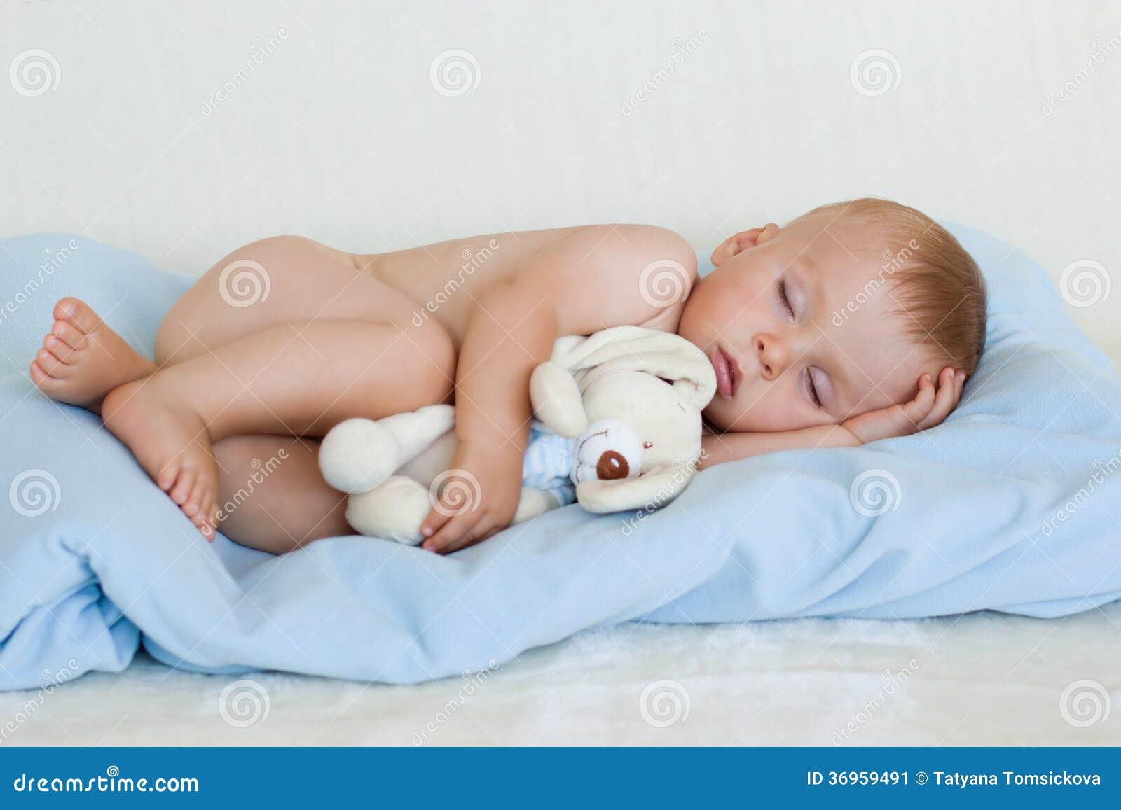 Petit bébé garçon, dormant avec le jouet de nounours