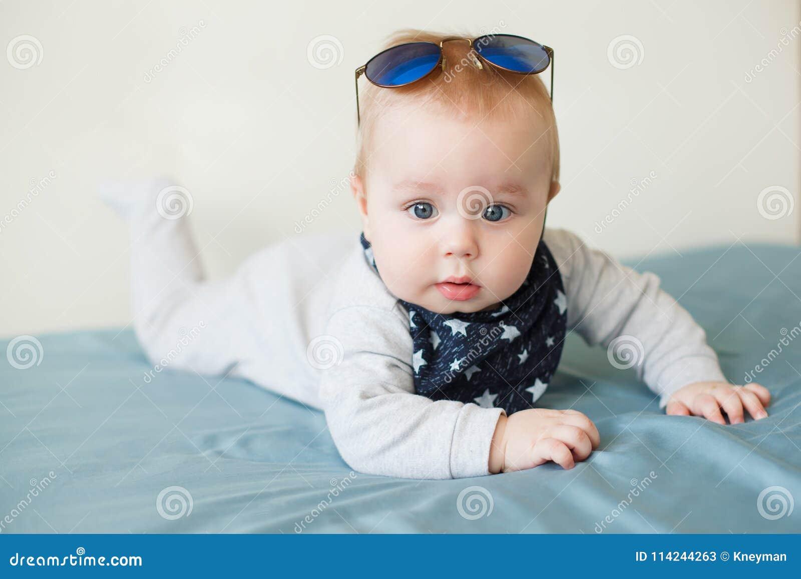 Petit bébé garçon drôle avec de grands yeux bleus et lunettes de soleil sur  sa tête 067e36b3972c